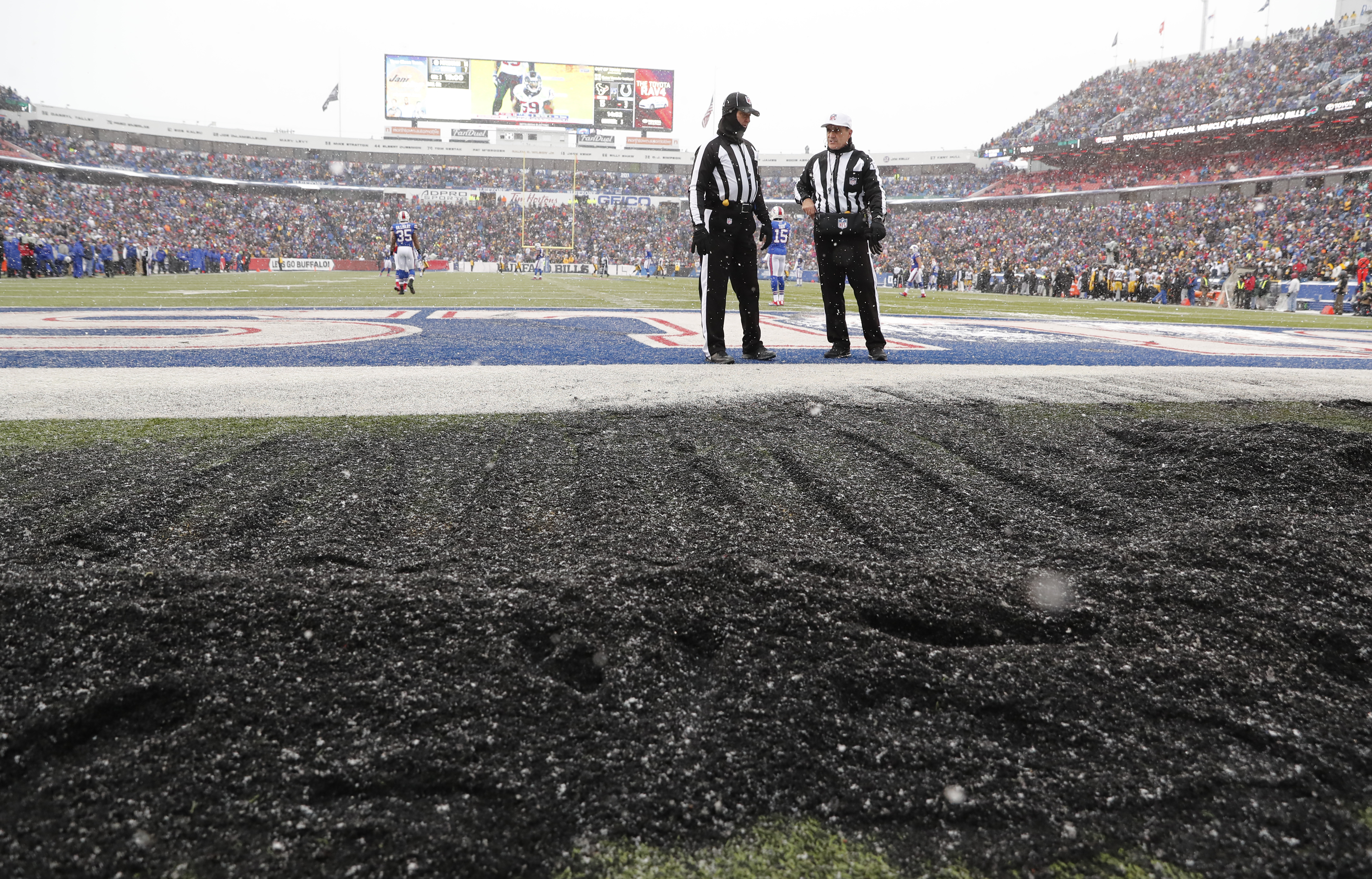 NFL referee Pete Morelli and back judge Greg Steed look over the rubber left on the field after halftime. (Harry Scull Jr./Buffalo News)