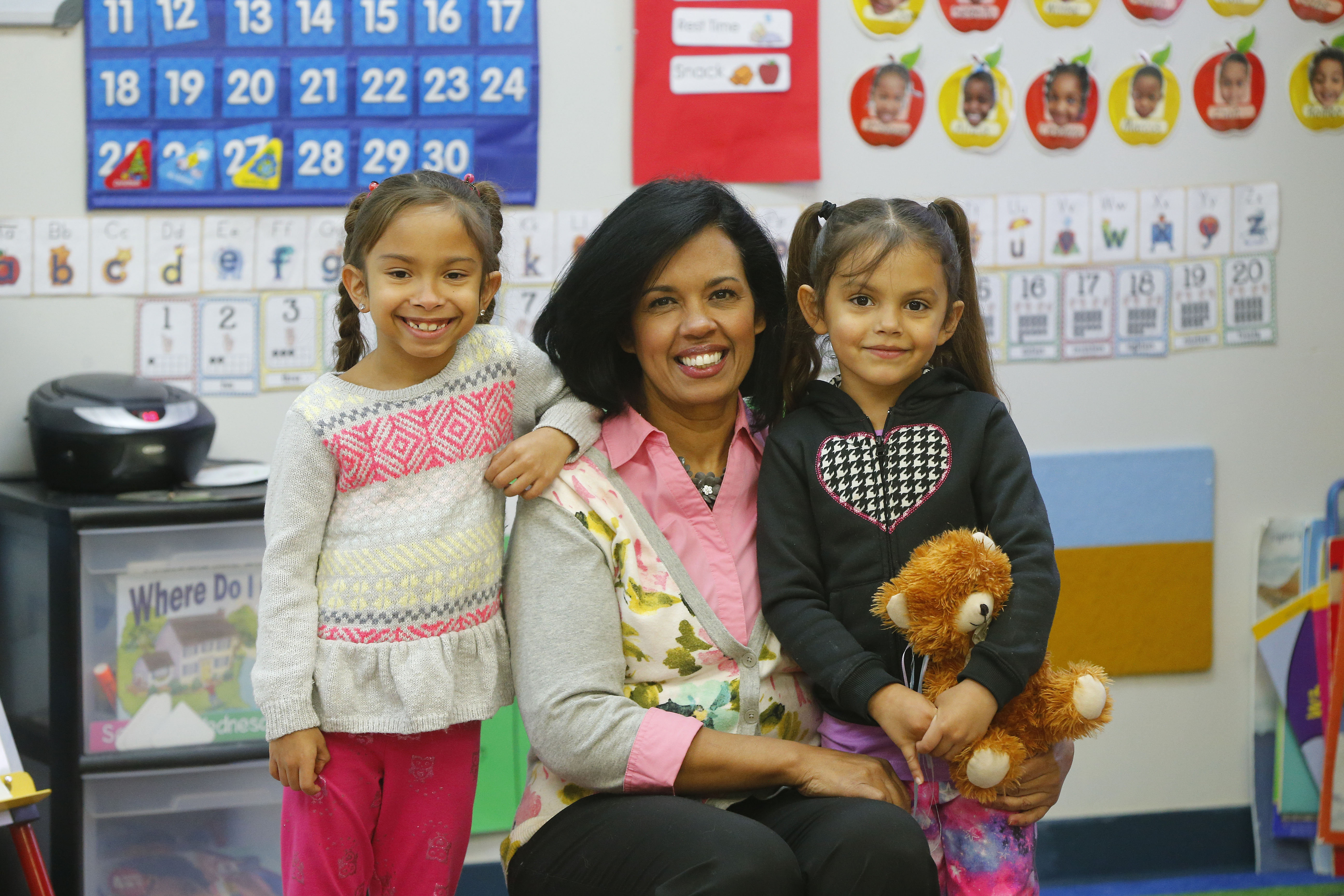 Dallas Lozada with her grandchildren Juliana Rivera, left, and Jayla Navarro, right, in Jayla's day care classroom at the Family Help Center in Buffalo. Lozada said she wouldn't have been able to keep her full-time job without child care assistance from Erie County. (Mark Mulville/Buffalo News)