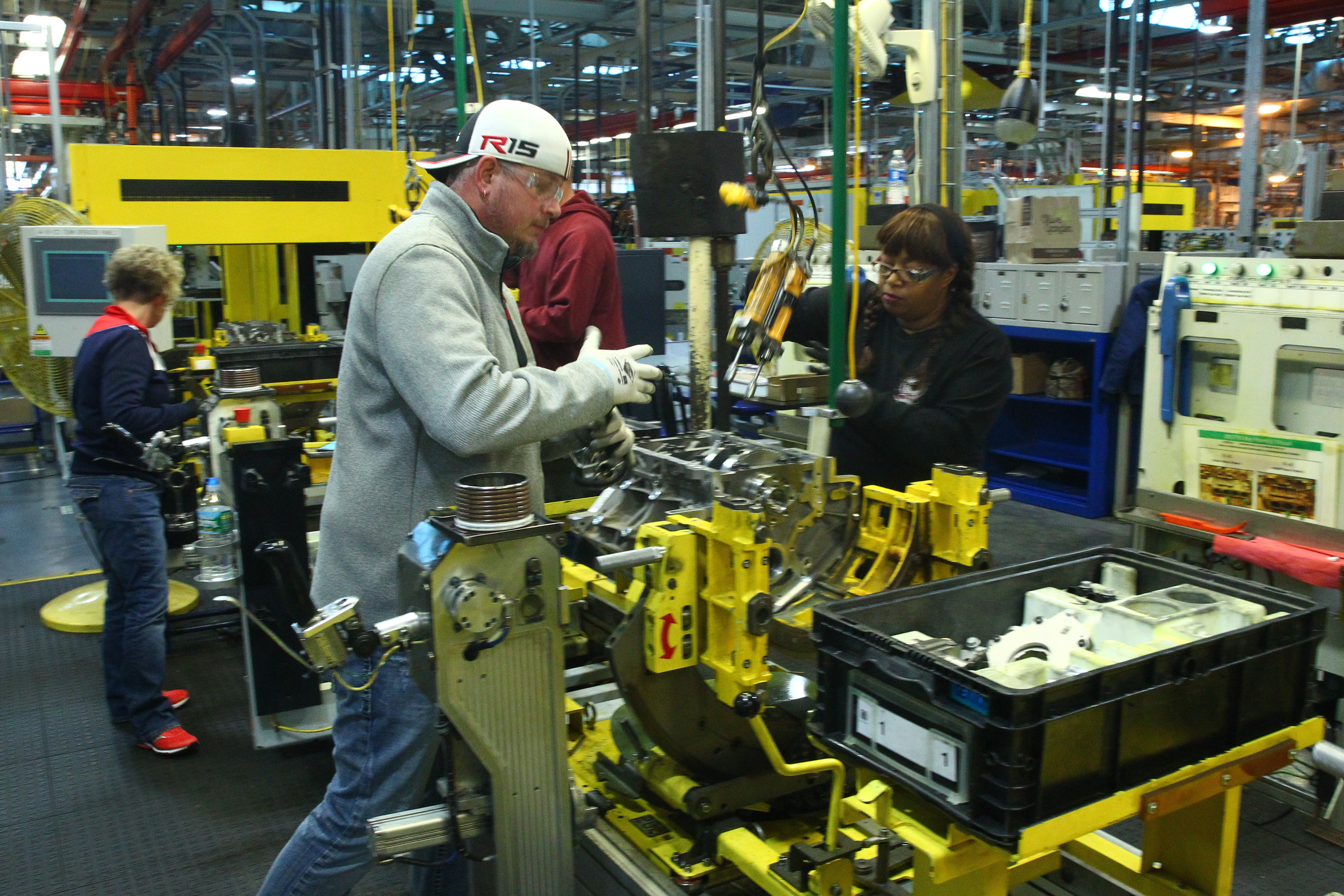 GM workers install rods and pistons in engines on assembly line  at GM Powertrain Tonawanda on Wednesday. (John Hickey/Buffalo News)