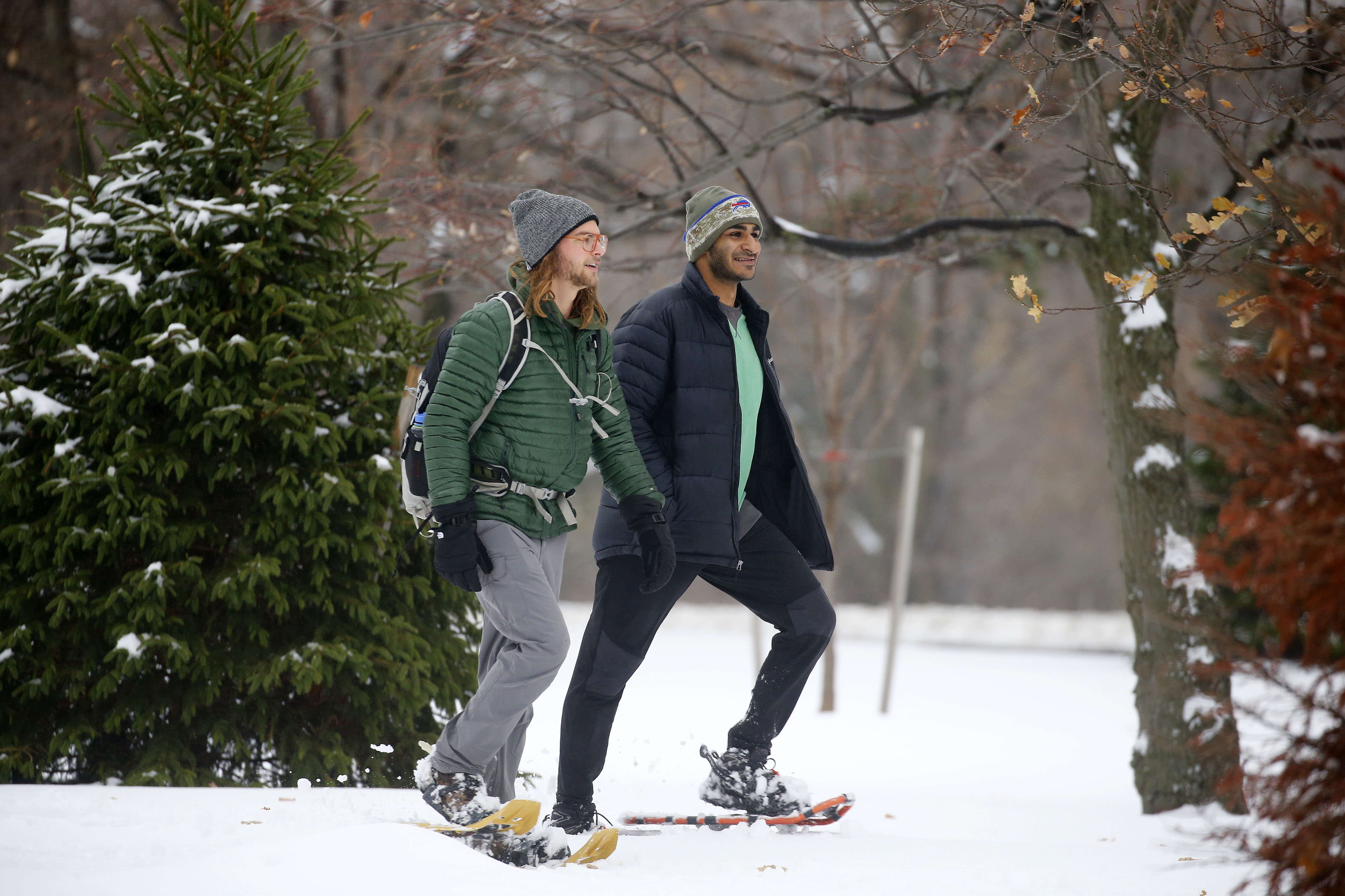 Simon Weinstein, left, and Matthew Asirwatham, right, snowshoe through Delaware Park in Buffalo on Saturday, Dec. 17, 2016.  (Mark Mulville/Buffalo News)