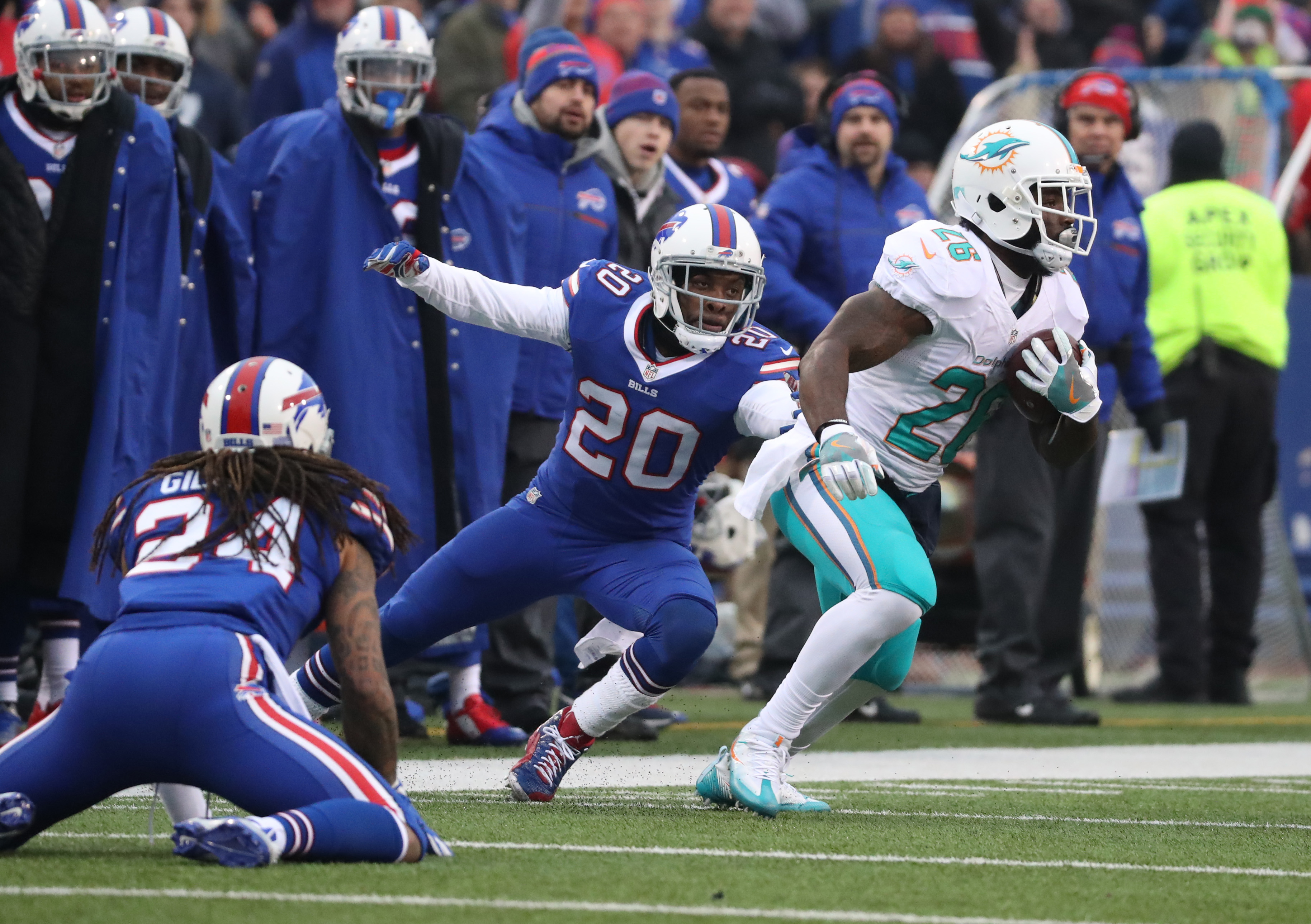 Miami Dolphins running back Damien Williams runs for a first down against Stephon Gilmore (24) and Corey Graham (20). (James P. McCoy/Buffalo News)