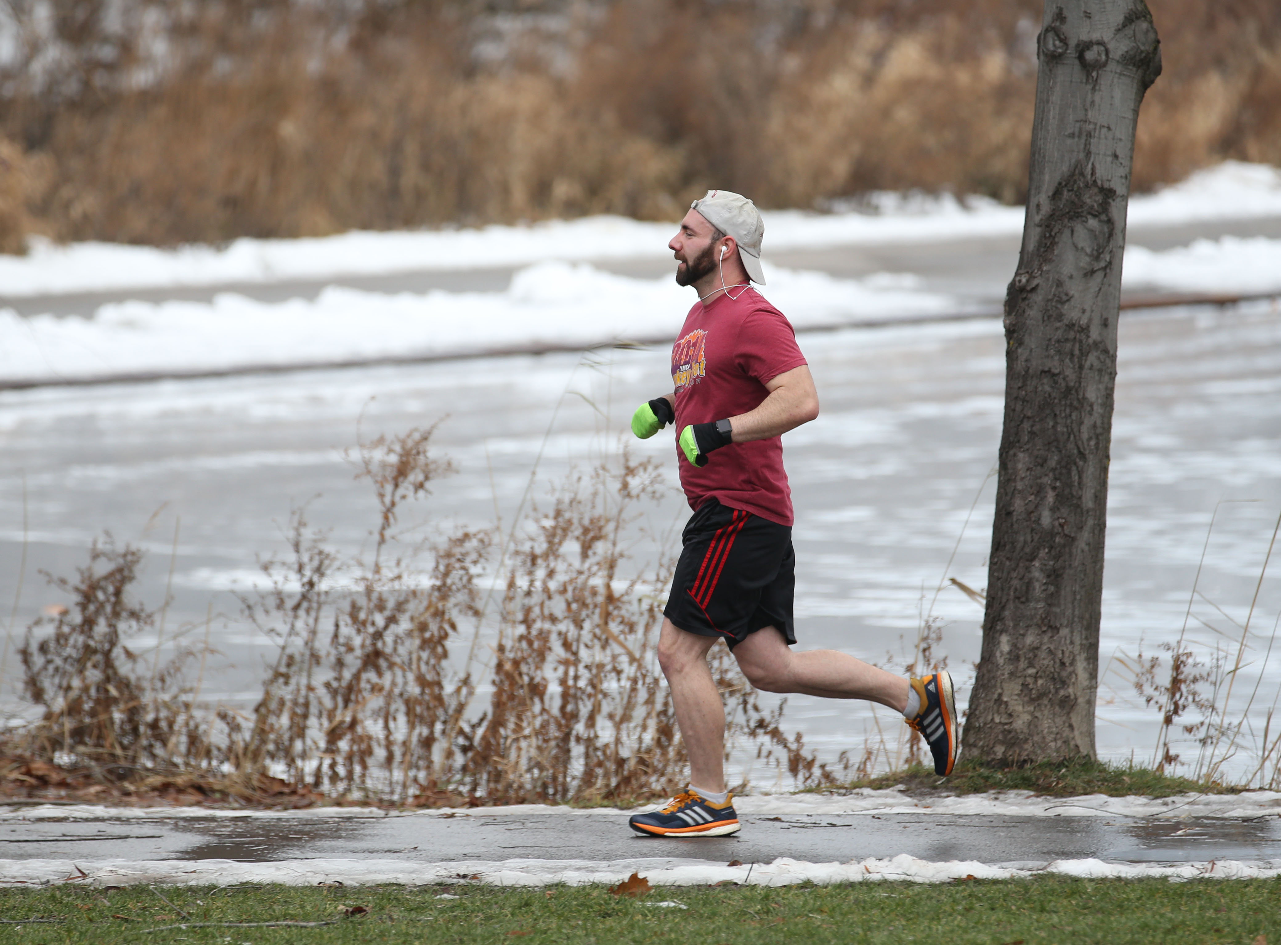 With a high of 55 degrees, Joshua Sanders runs around Hoyt Lake in Delaware Park in shorts and a T-shirt on Monday, Dec. 26, 2016. (Sharon Cantillon/Buffalo News)