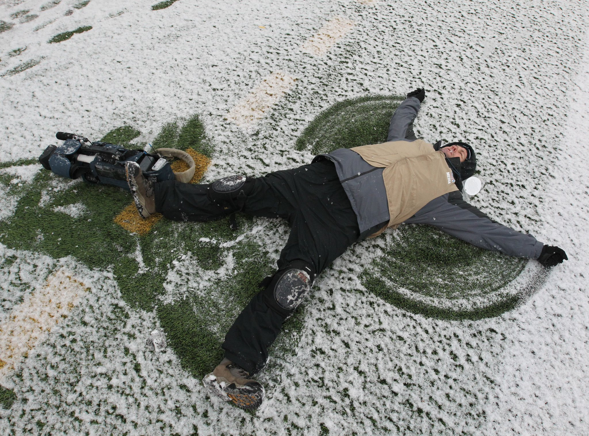 Some people are enjoying today's snow – Scott Swenson took advantage of it to make a snow angel during the Bills/Steelers game – but it could lead to dangerously icy roads tonight. (James P. McCoy/Buffalo News)