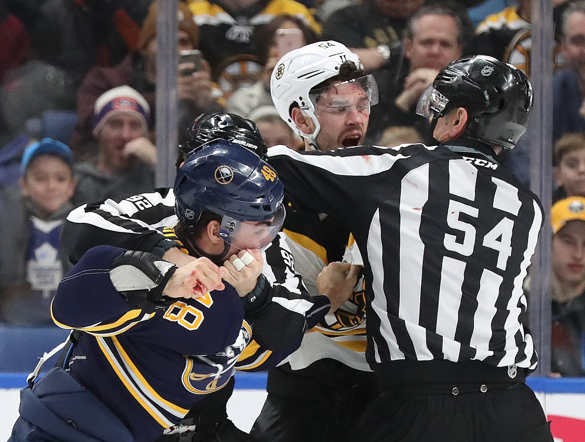 Sabres rookie William Carrier bloodied his hand on the visor of Boston's Adam McQuaid. (James P. McCoy/Buffalo News)
