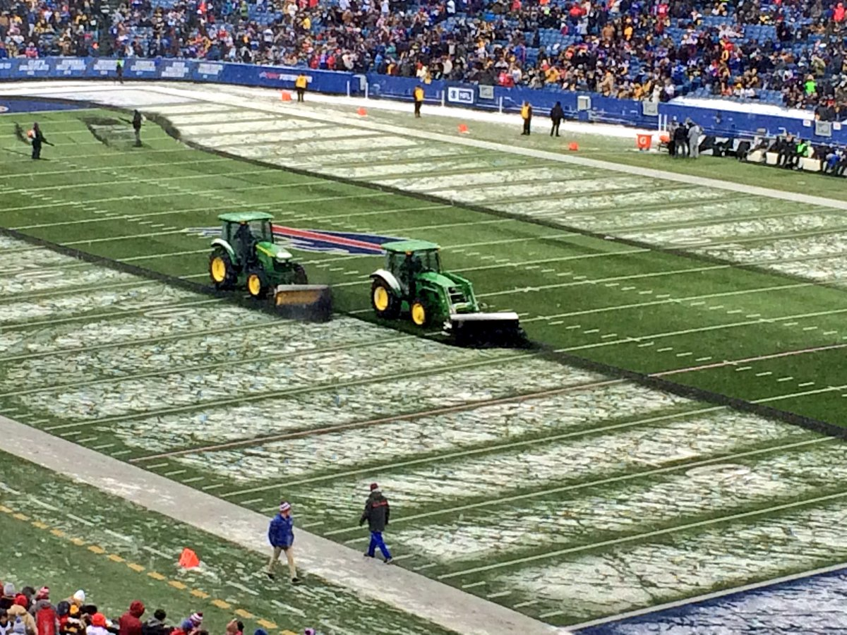 Tractors aim to remove snow from the field at halftime (Nick Veronica/Buffalo News)