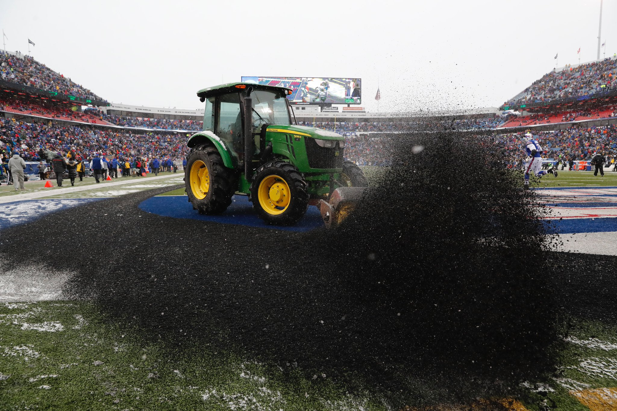 Tractors that were called upon to clear snow off the field ended up pushing up rubber pellets, which piled up around the perimeter of the field. (Harry Scull Jr./Buffalo News)