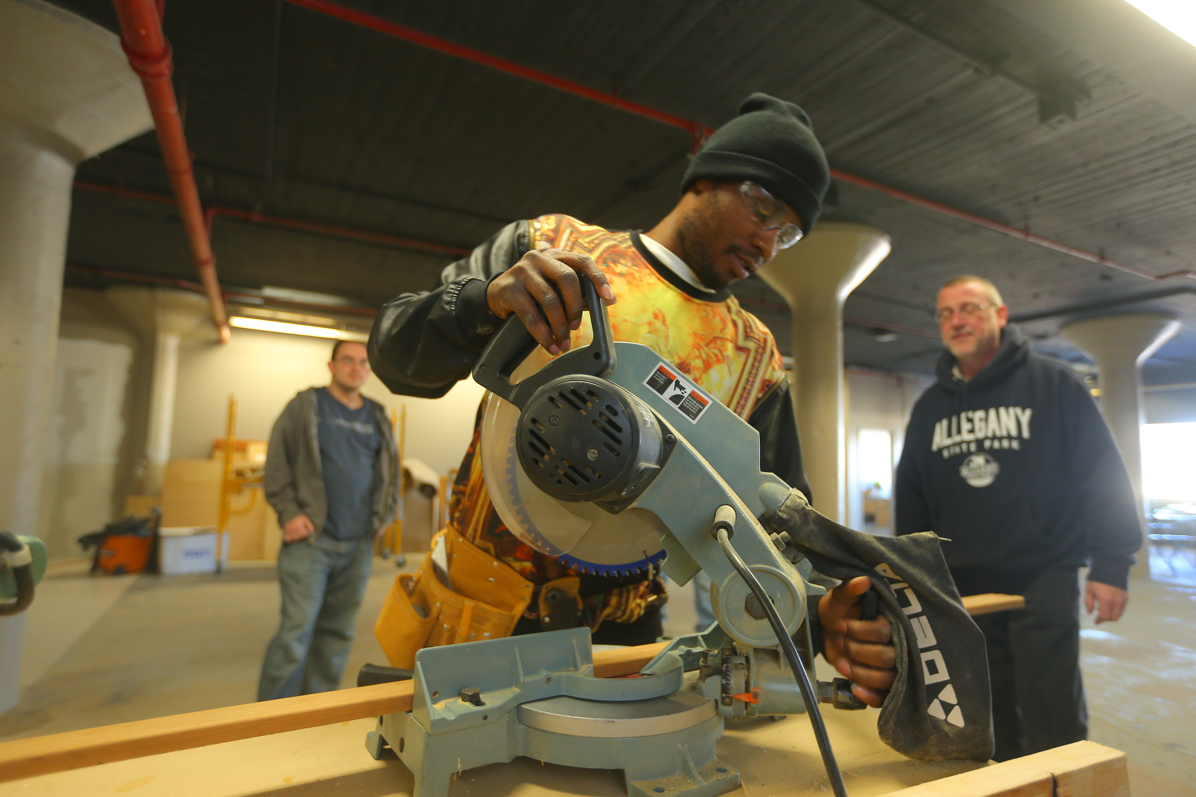 Spencer Williams , left, sets up a chop saw under the supervision of instructor Paul Crawford at the Isaiah 61 training program in Lockport on on  Wednesday,  Dec. 14, 2016. The program teaches building trades skills to unemployed adults in a classroom and practice center on the third floor of Harrison Place in Lockport, N.Y. Later, the students will help renovate abandoned houses purchased by  Isaiah 61, a faith-based group. (John Hickey/Buffalo News)
