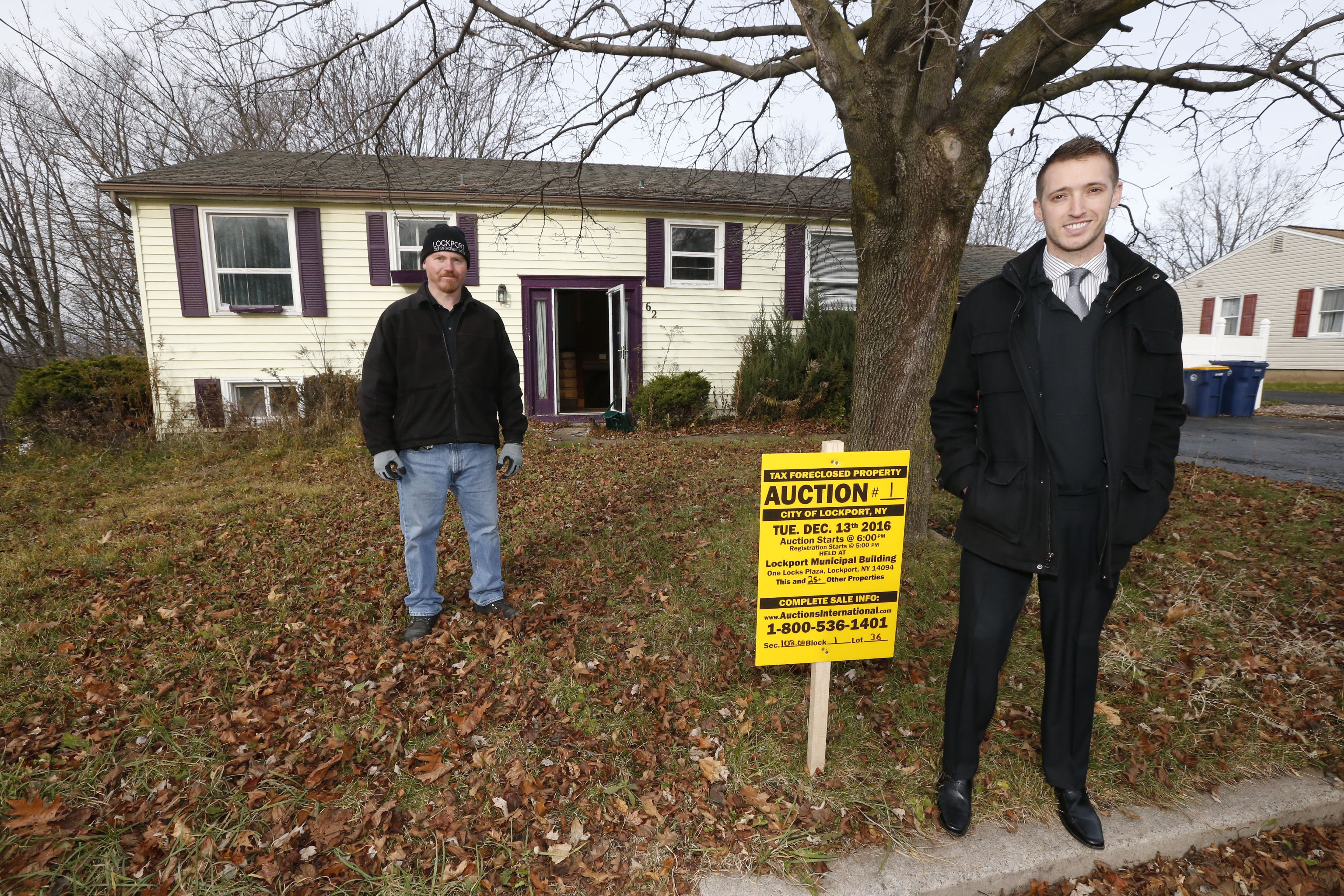 Brian Smith, Lockport director of planning and development, right, and Clayton Dimmick, Lockport's senior building inspector, survey a home at 62 Hillcrest Drive on Tuesday, Dec. 6, 2016. The home will be auctioned soon. (Robert Kirkham/Buffalo News)
