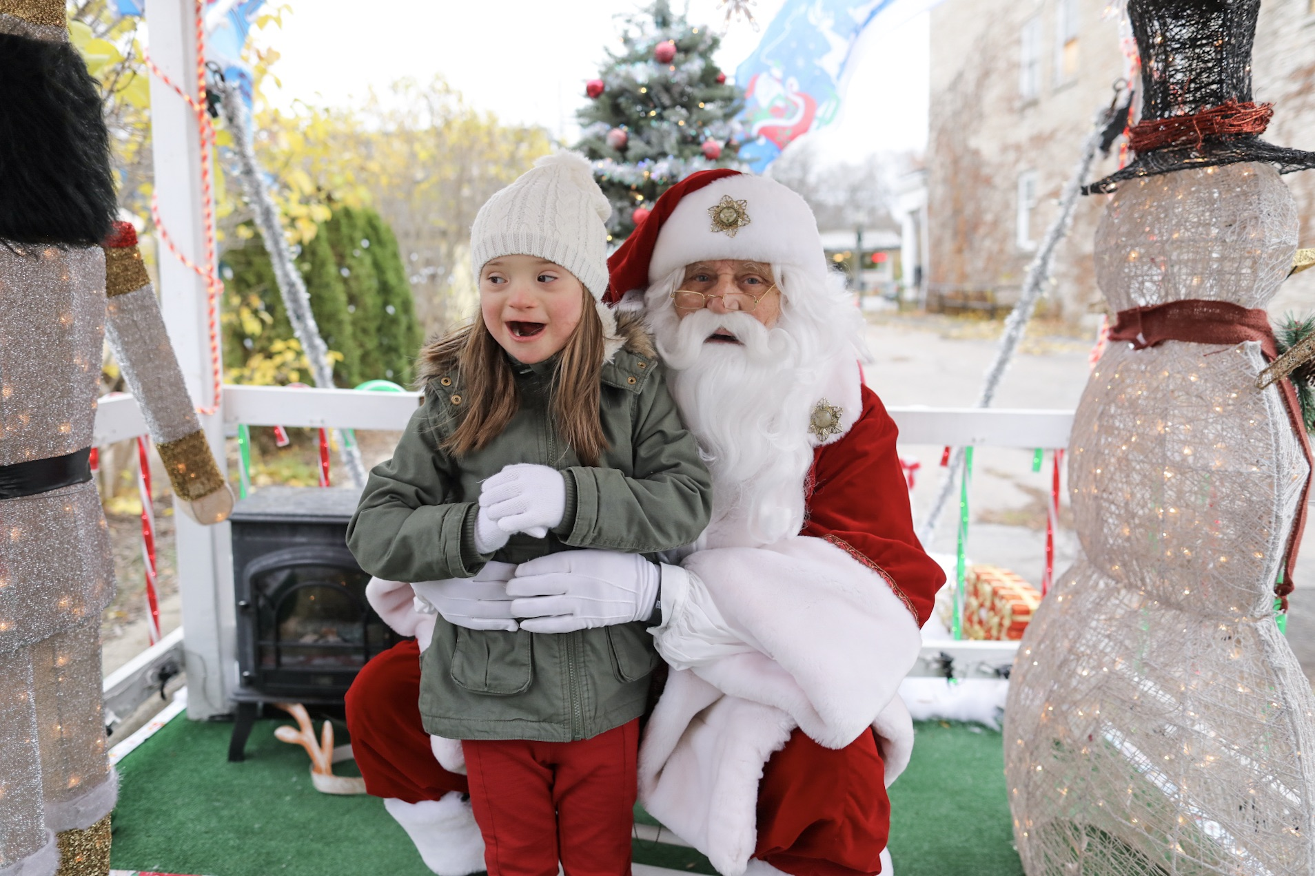 """Six-year-old Lyla Dolly stands next to Santa Claus on Dec. 3, 2016 in Lewiston, N.Y. Charles """"Vince"""" Canosa, 71, has been dressing up as Santa for 50 years. For the past four years, hundreds of kids at the Lewiston Christmas Walk have told him each year what they want for Christmas. (Photo by Jessica Dolly)"""