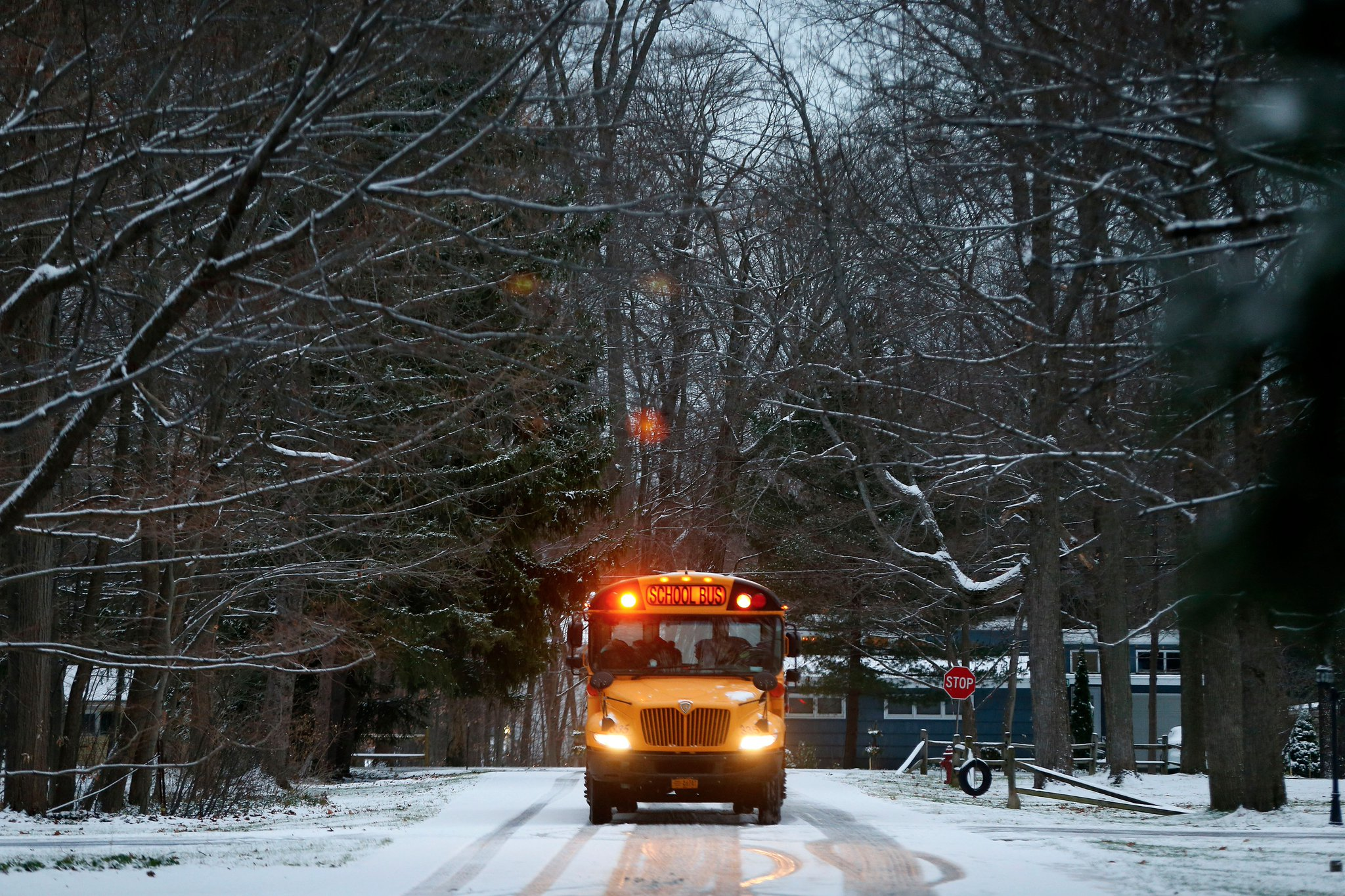 Roads are covered in snow as a school bus makes a stop in Orchard Park. (Mark Mulville/Buffalo News)