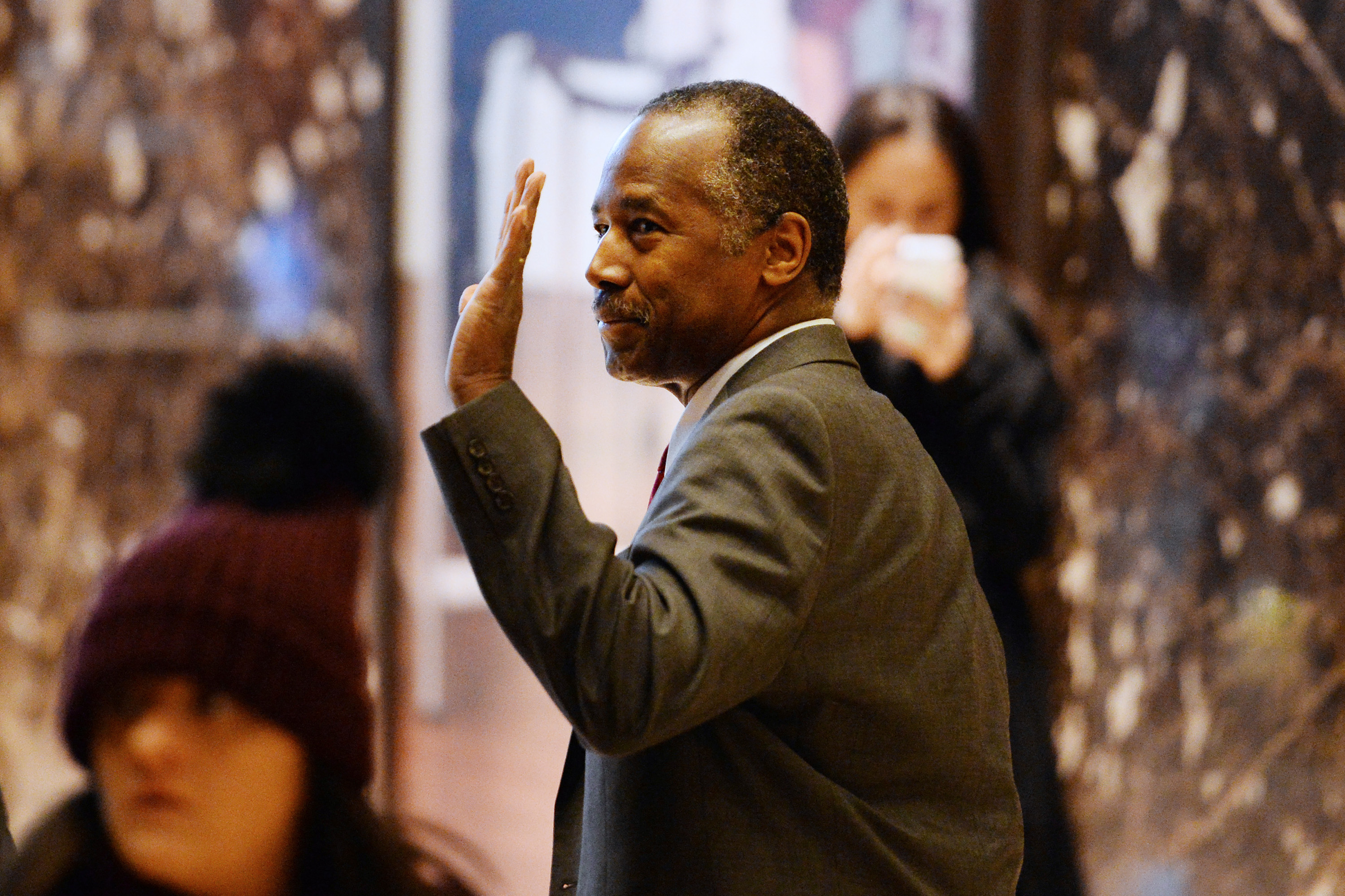 Ben Carson waves to bystanders as he walks through the lobby of the Trump Tower in New York City on Nov. 22, 2016. (Anthony Behar/CNP/Zuma Press/TNS)