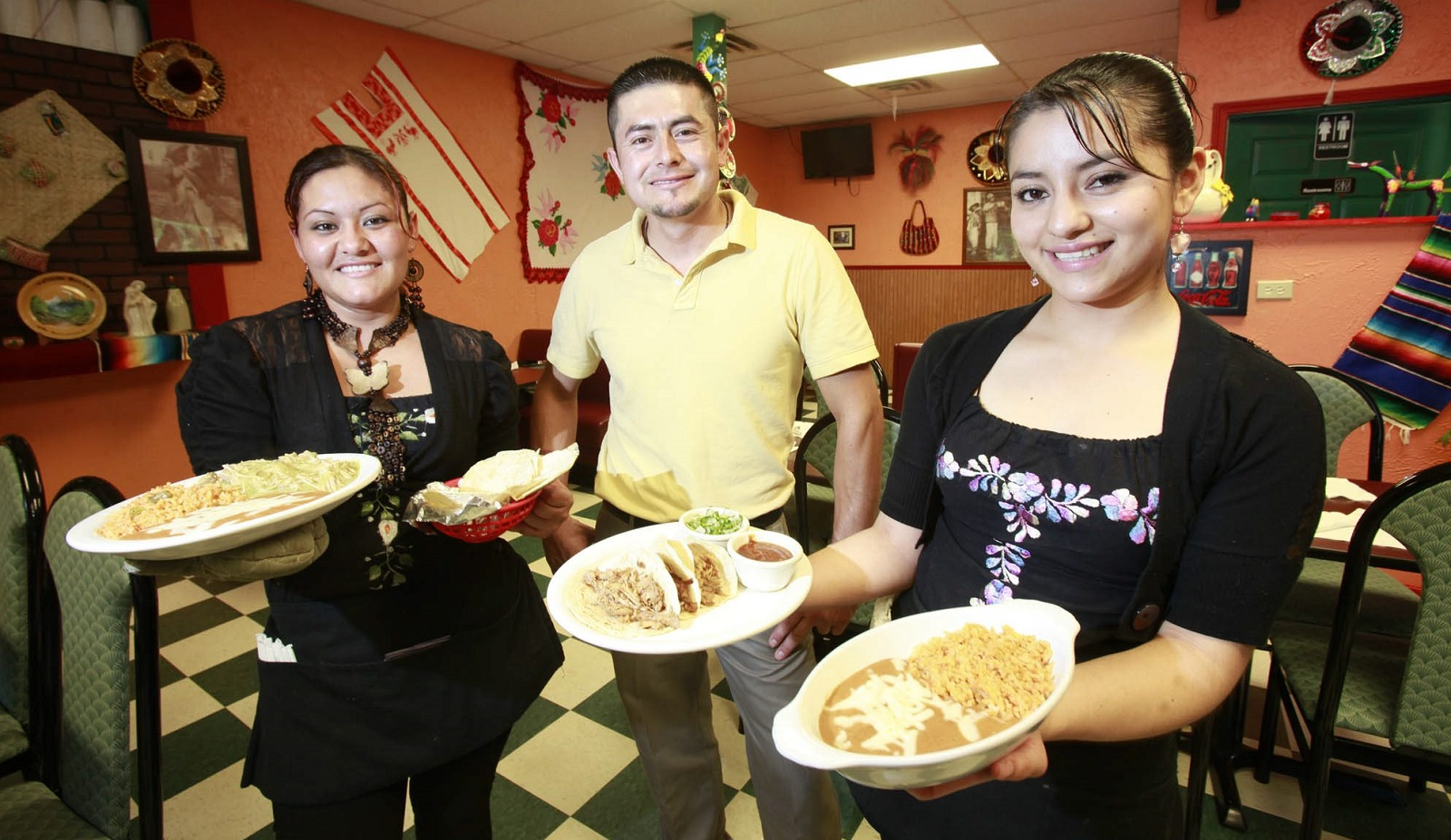 From left to right: Waitress Nelly Gallicia, co-owner Leonel Rosario, and waitress Elva Rosario as they hold plates of chili verde, and taco carnitas, at Mariachi de Oro. (Harry Scull Jr./Buffalo News)