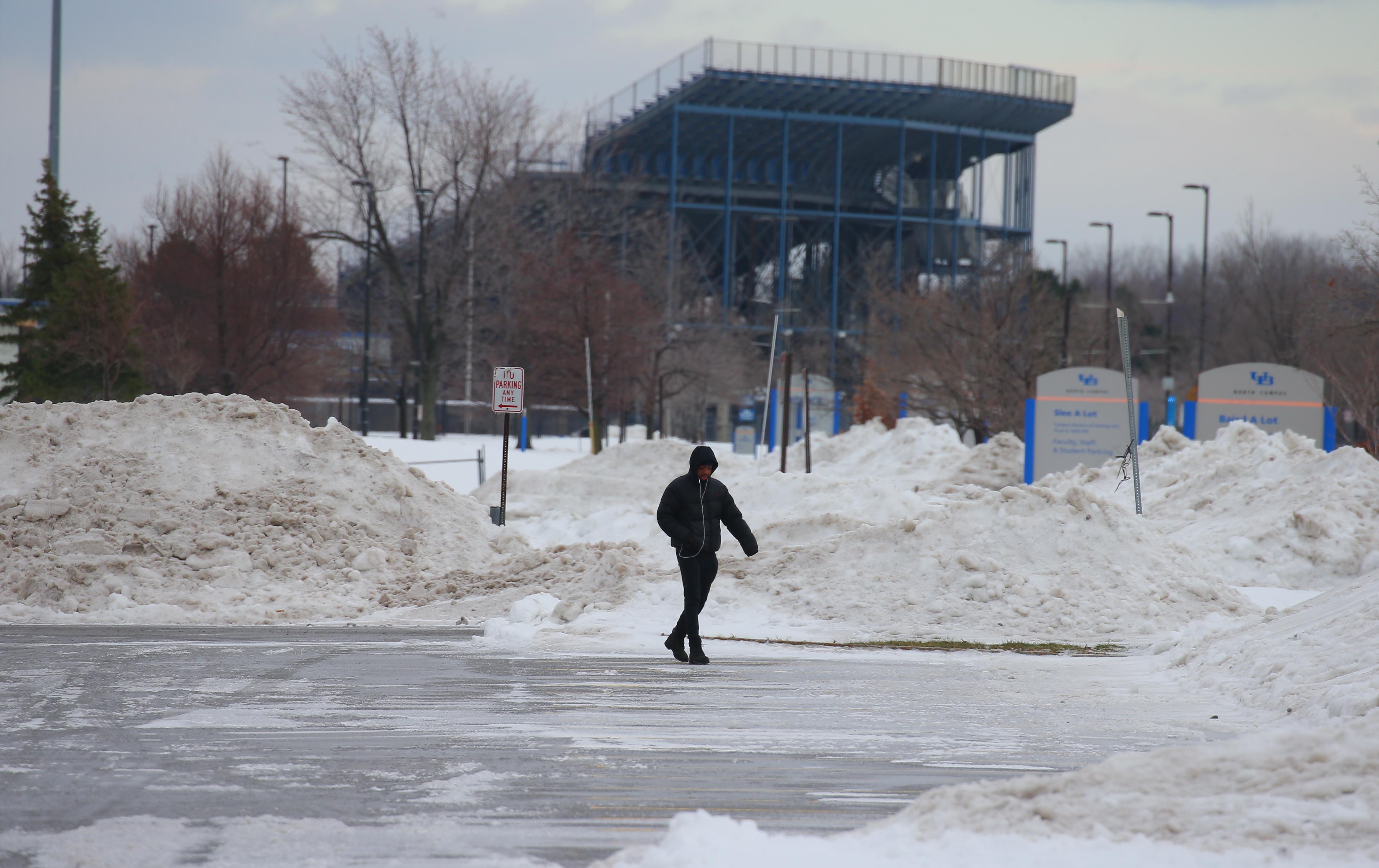 A pedestrian navigates an icy parking lot at the University at Buffalo's Amherst campus on  Sunday,  Dec. 18, 2016. (John Hickey/Buffalo News)