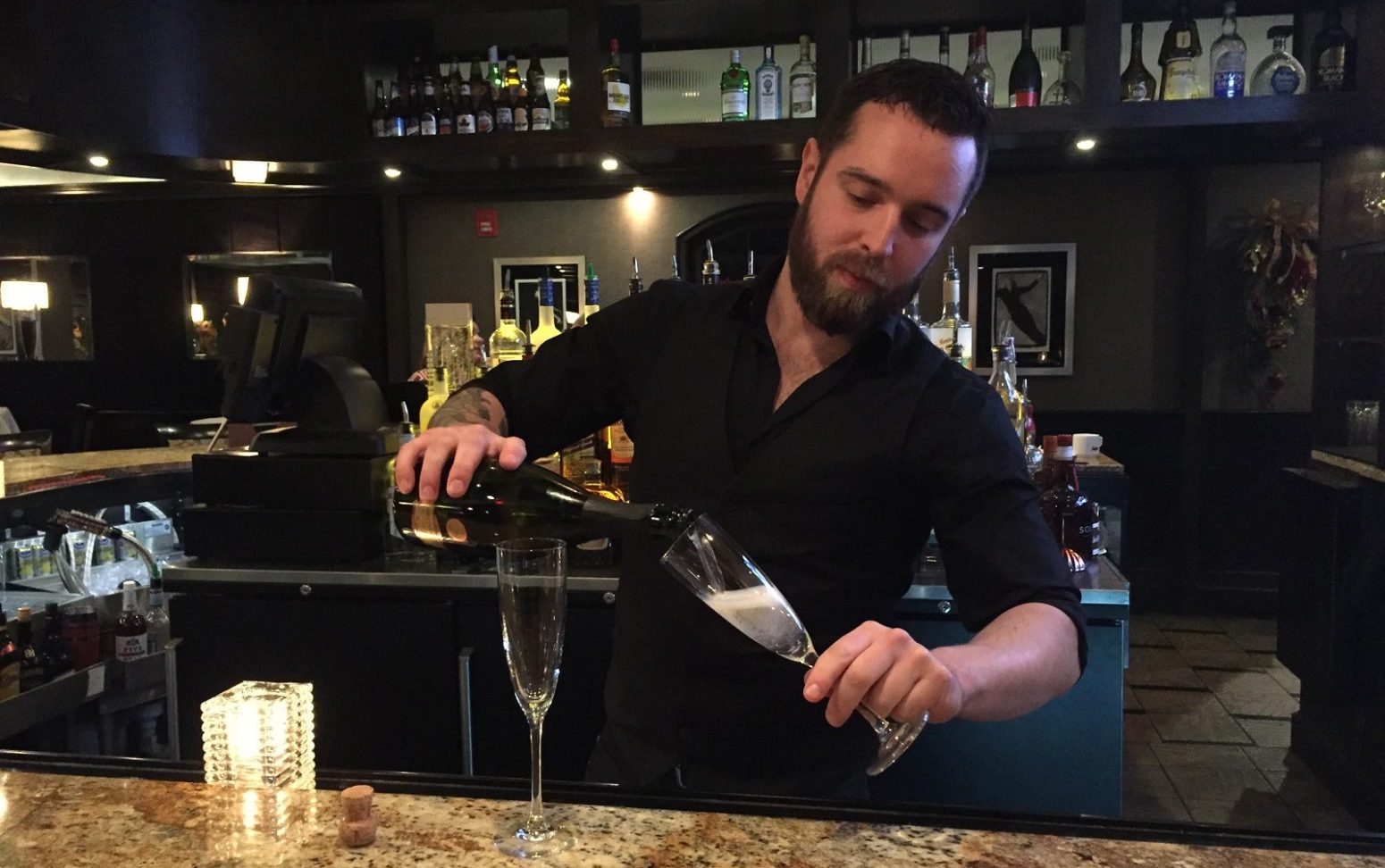 Jonny Reff, bartender at the 31 Club, said the glass should be held at a 45-degree angle when pouring champagne. (Elizabeth Carey/Special to The News)