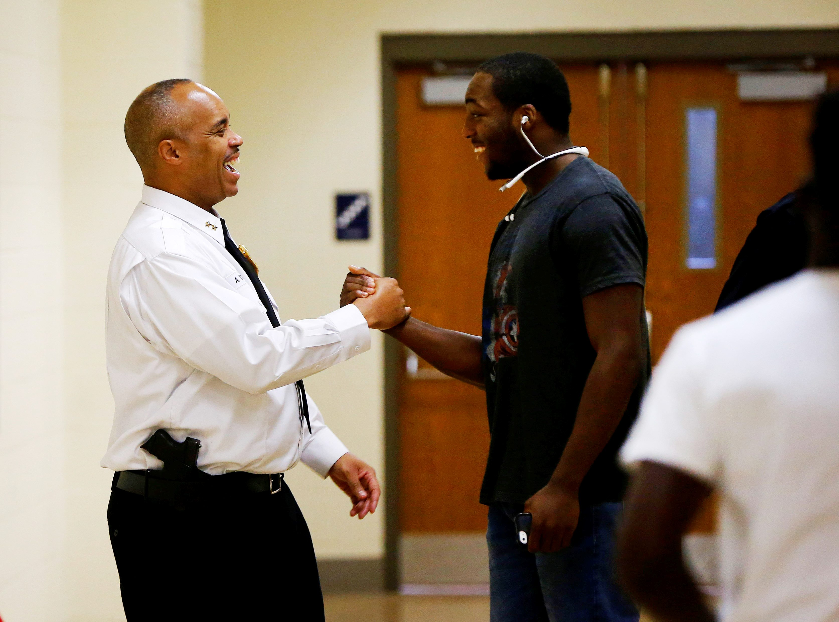 Schools Resource Chief Aaron Young greets a students in the hallway at Bennett High School. (Mark Mulville/Buffalo News)
