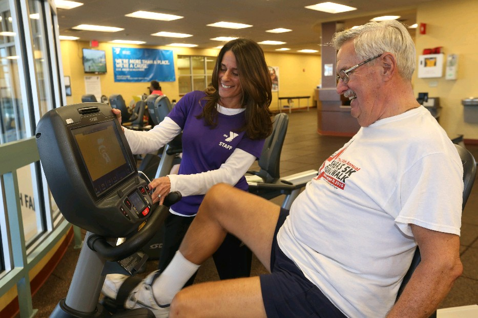 Personal trainer Renae Sykes works with Joe Dunn on the exercise bike at the Independent Health Family Branch YMCA in Williamsville. (Sharon Cantillon/Buffalo News)