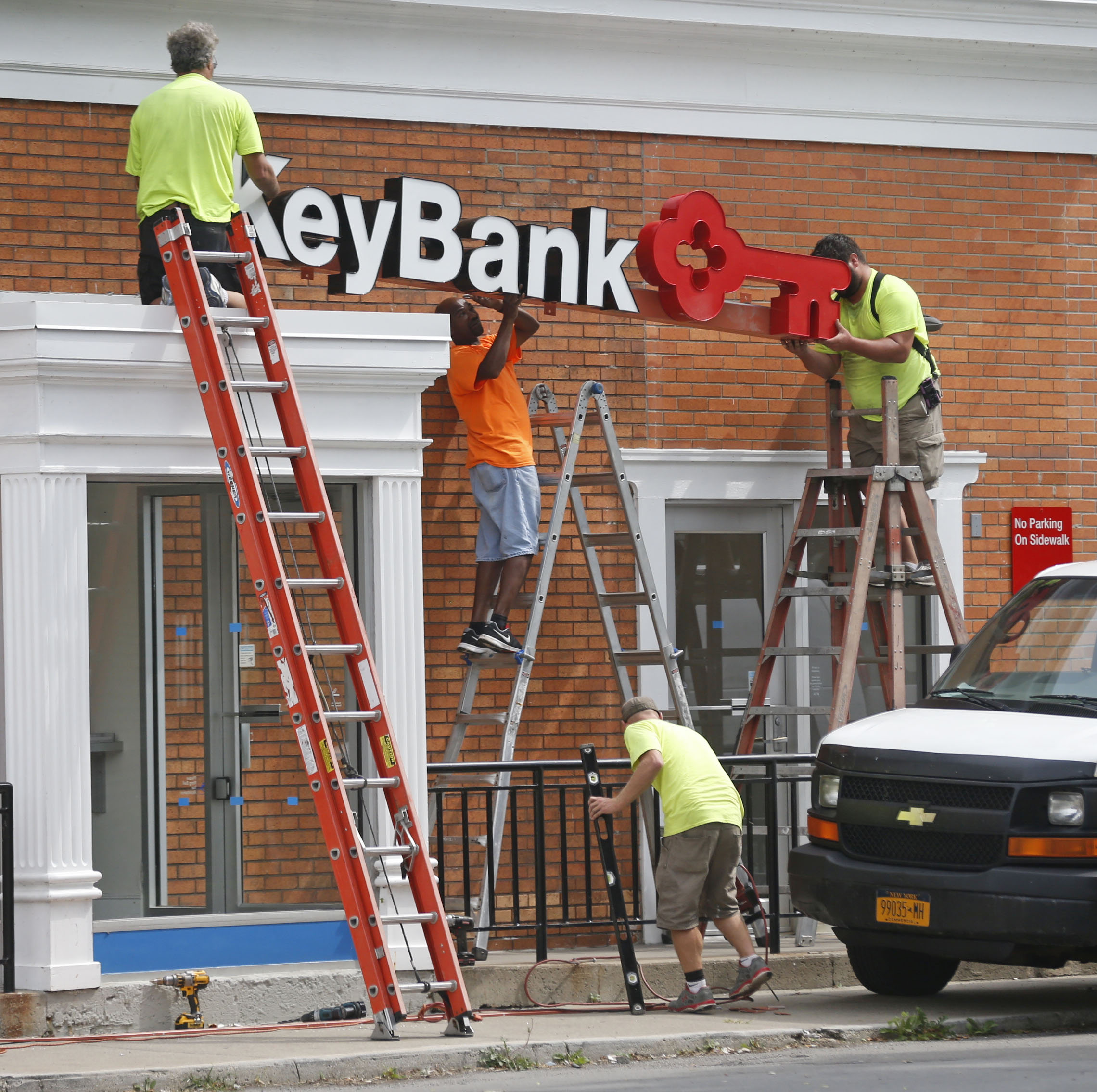 Contractors install a KeyBank sign after removing a First Niagara logo on the bank branch at the corner of Willett and Clinton streets in Buffalo last fall. Key completed its acquisition of First Niagara last summer. (Robert Kirkham/Buffalo News file photo)