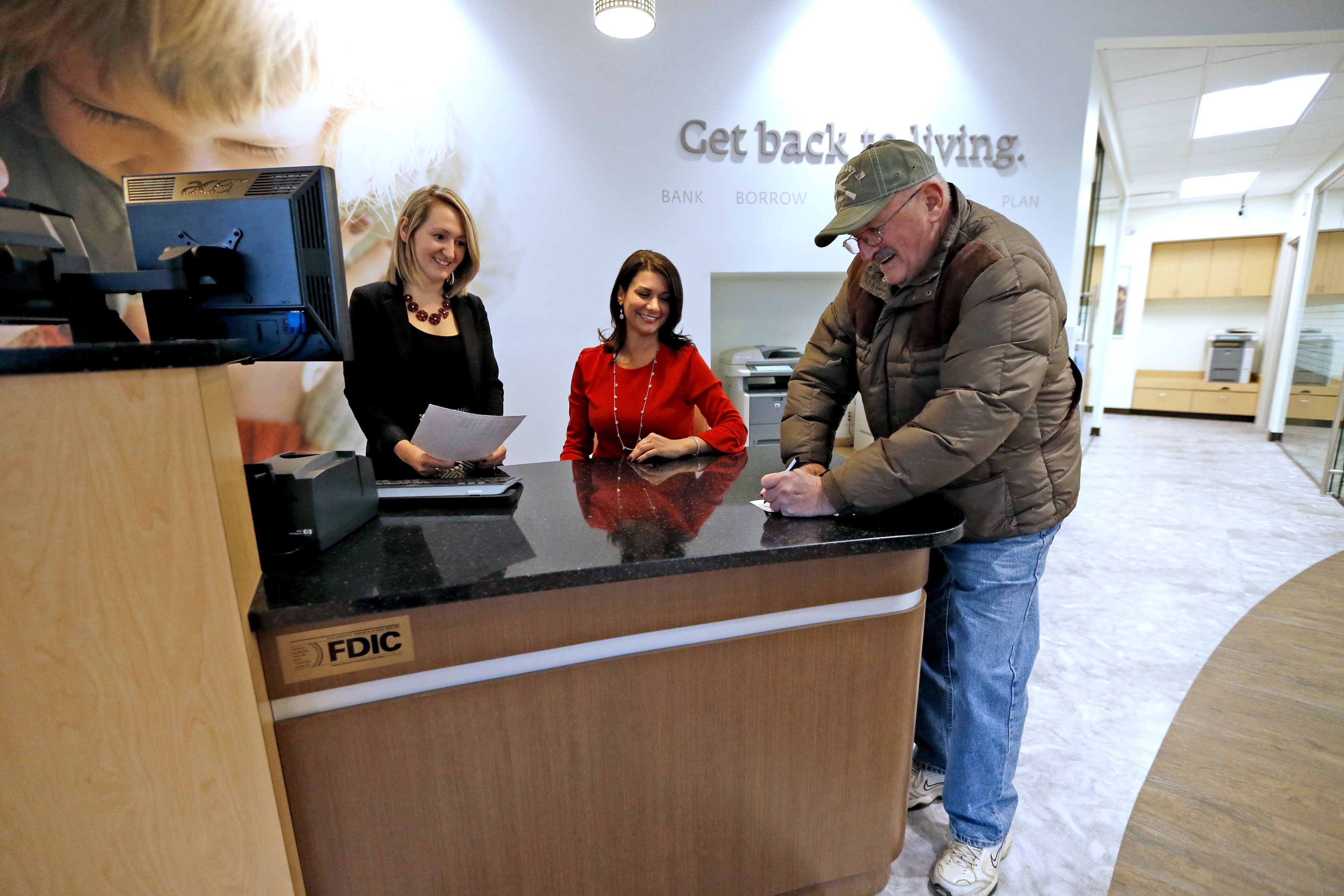Northwest Bank employees Vanessa Prokop and Sara Manigross wait on Jim Michalczak of Orchard Park at the new open-concept branch in Orchard Park. (Robert Kirkham/Buffalo News)