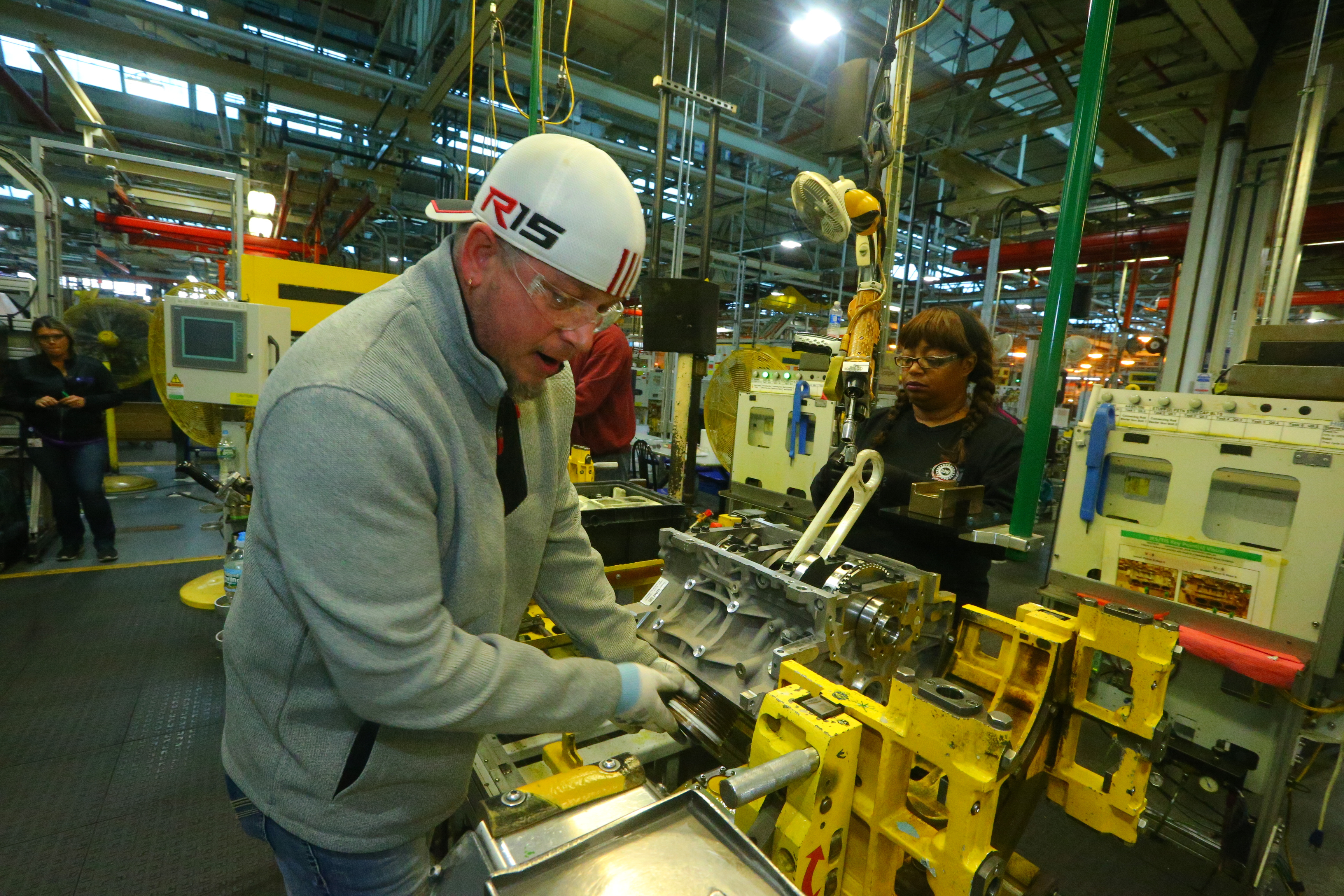 GM workers install rods and pistons in engines on assembly line  at GM Powertrain Tonawanda engine plant in December. (John Hickey/Buffalo News file photo)
