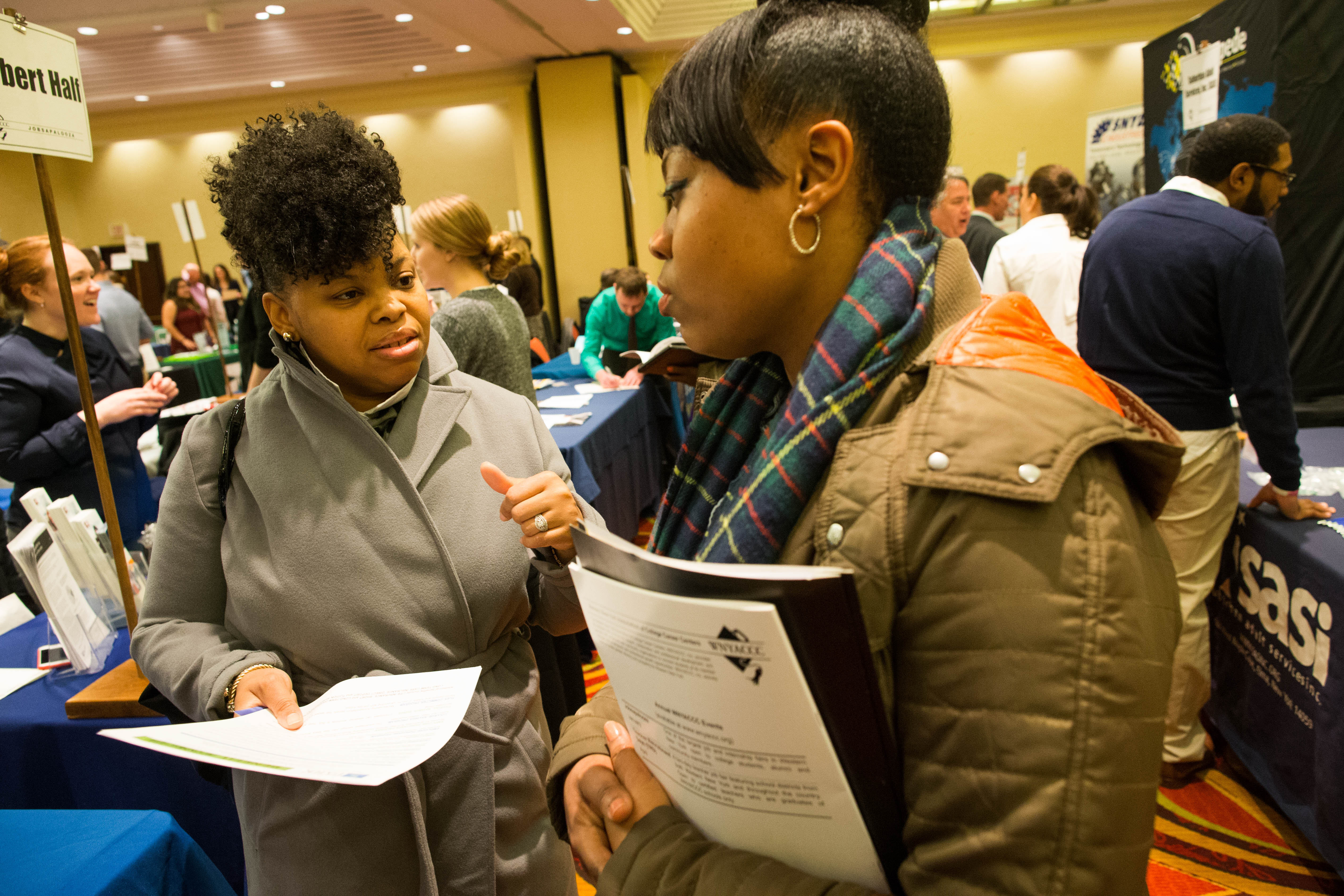Job seekers Chelitta Spencer, left, and Darcel Blue chat during the Jobsapalooza career fair at the Buffalo Niagara Marriott in Amherst earlier this month.  (Derek Gee/Buffalo News)
