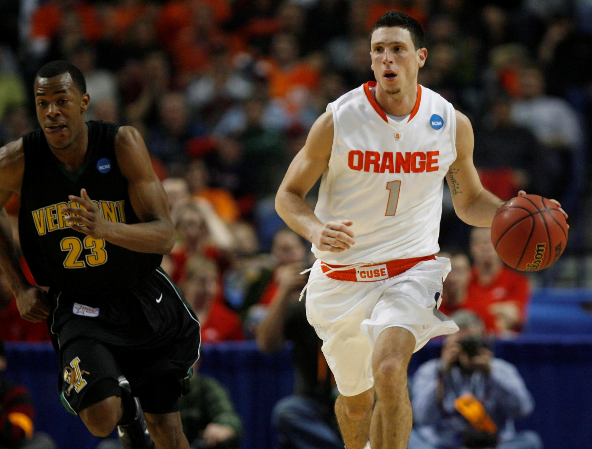Syracuse's Andy Rautins brings the ball up court as Vermont's Marquis Blakely trails. (John Hickey/Buffalo News}