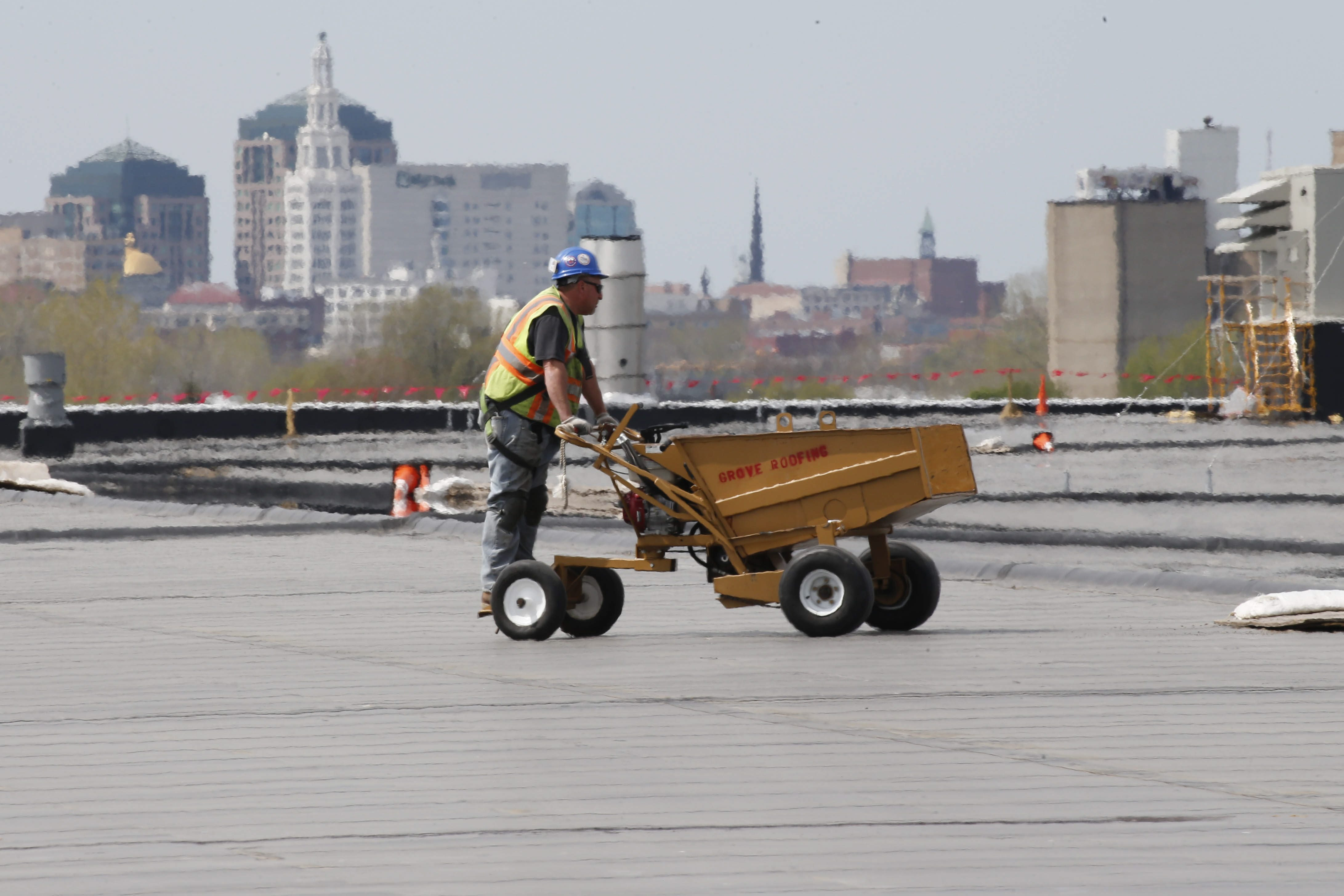 A worker drives equipment across the roof of the massive SolarCity manufacturing facility at RiverBend in May. The factory was constructed as part of the state's Buffalo Billion economic development program. (Derek Gee/Buffalo News file photo)
