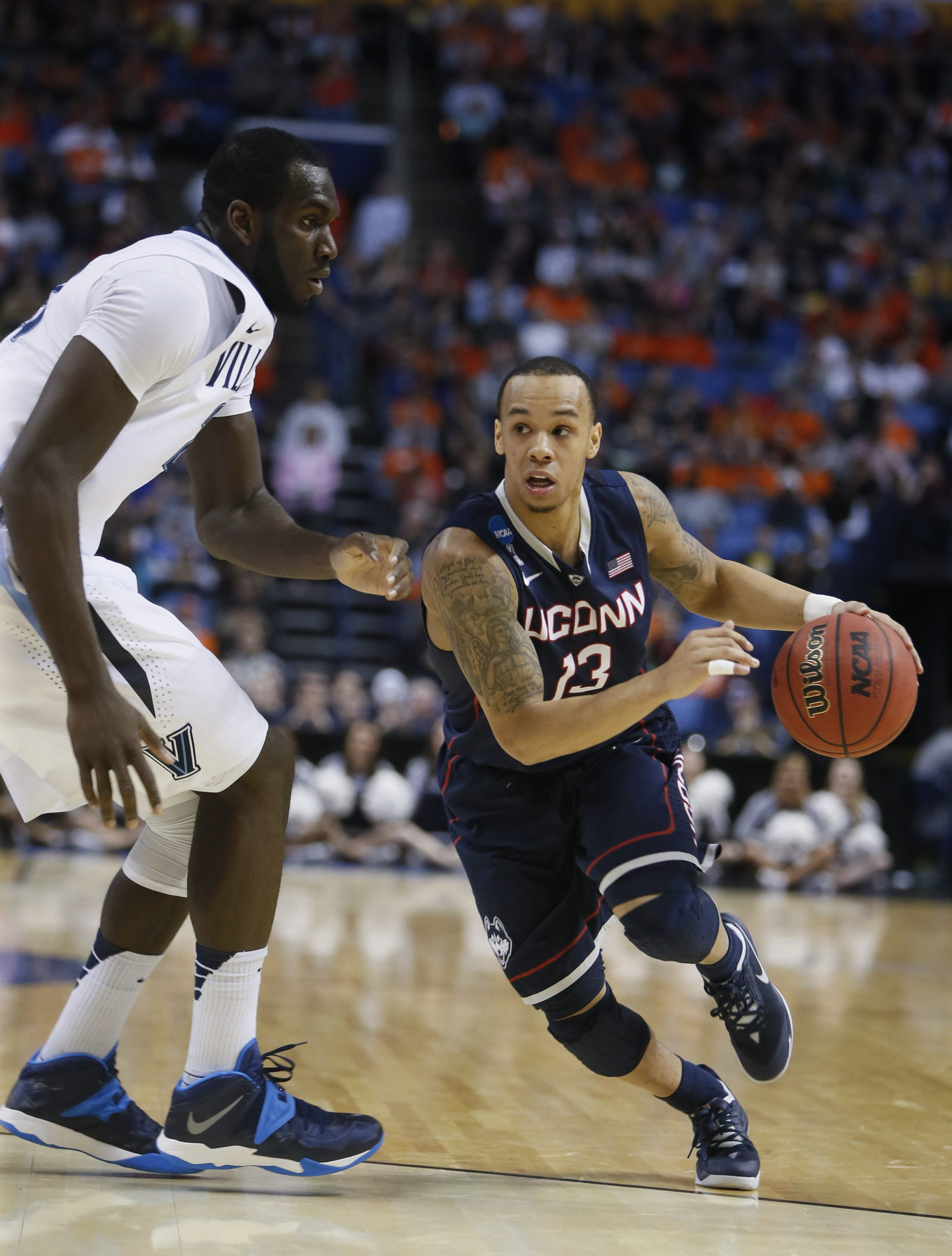 UConn's Shabazz Napier (13) drives the ball past Villanova's Daniel Ochefu, left, during the first half of the third-round game in the men's NCAA college basketball tournament at First Niagara Center, Saturday, March 22, 2014.  (Mark Mulville/Buffalo News)