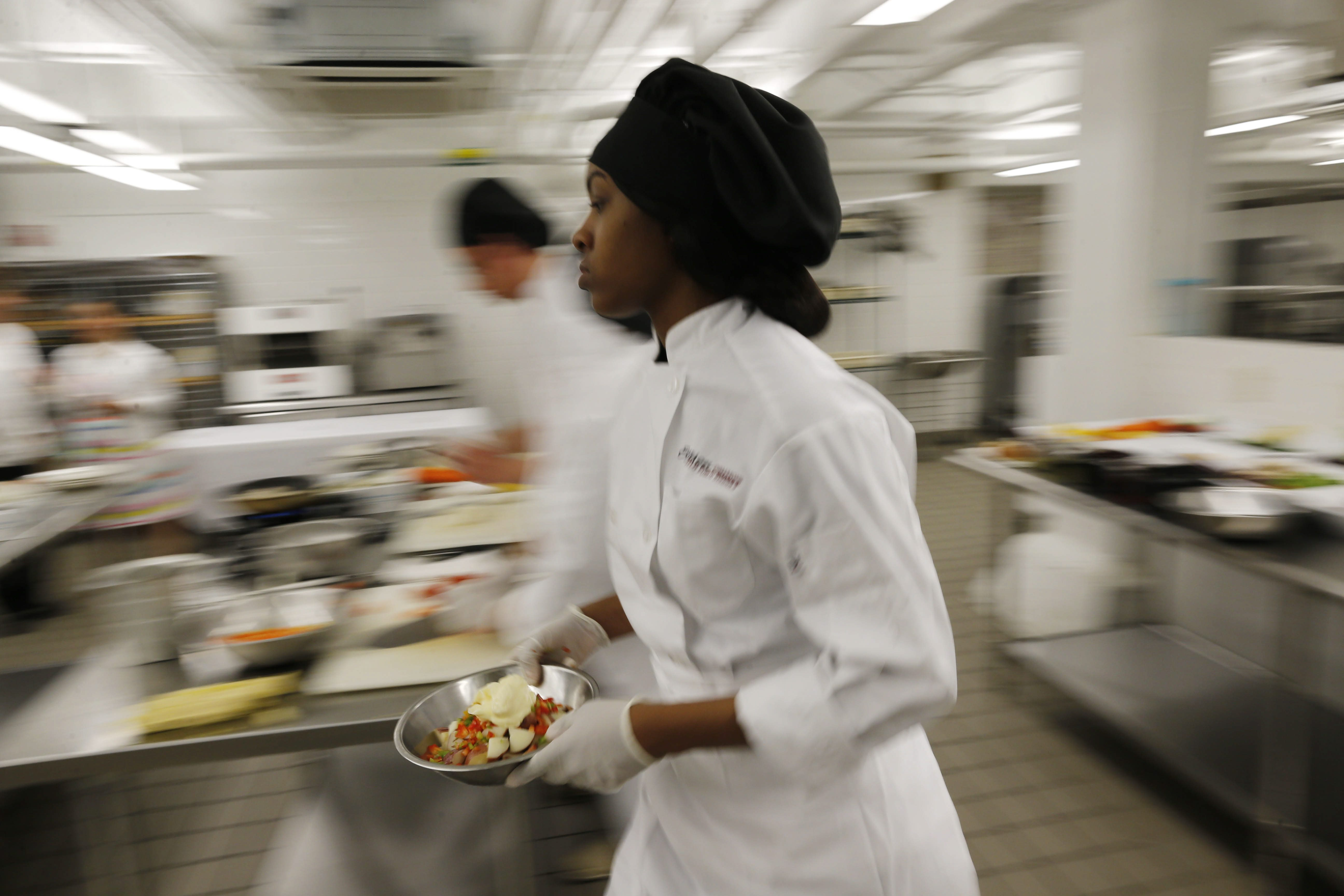Emerson School of Hospitality junior Da'Vyne Brown rushes back to her station with ingredients while competing in an 'Iron Chef' style cooking competition in June 2016. Developers hope to win a bid with Buffalo Public Schools to develop a second culinary schoool in downtown Buffalo. (Derek Gee/Buffalo News file photo)