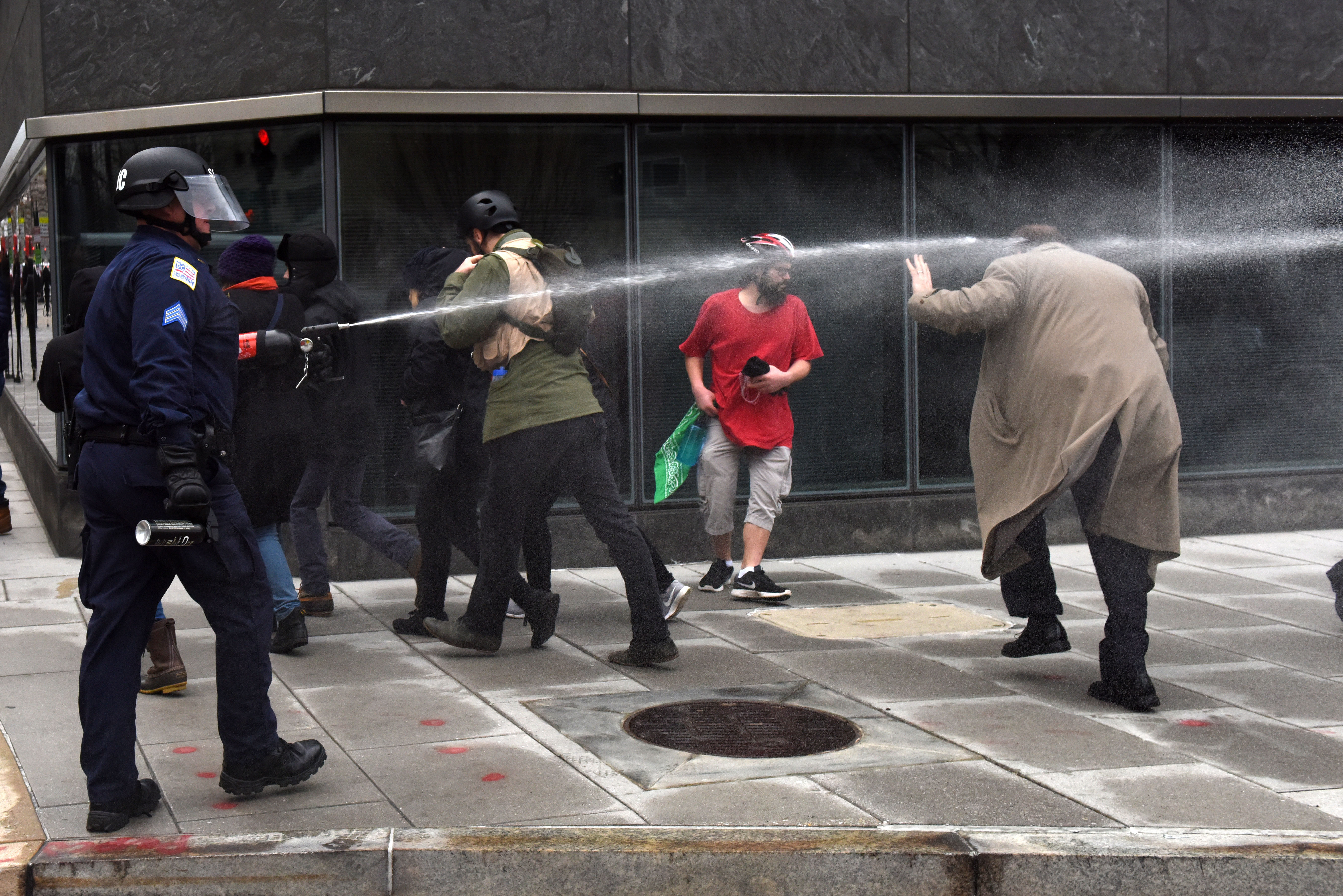 A man is pepper sprayed at the corner of 12th and I St. N.W. in Washington on Jan. 20. Police responded to a vandalizing group of protesters with pepper spray to disperse the protesters. (Washington Post photo by Michael Robinson Chavez)