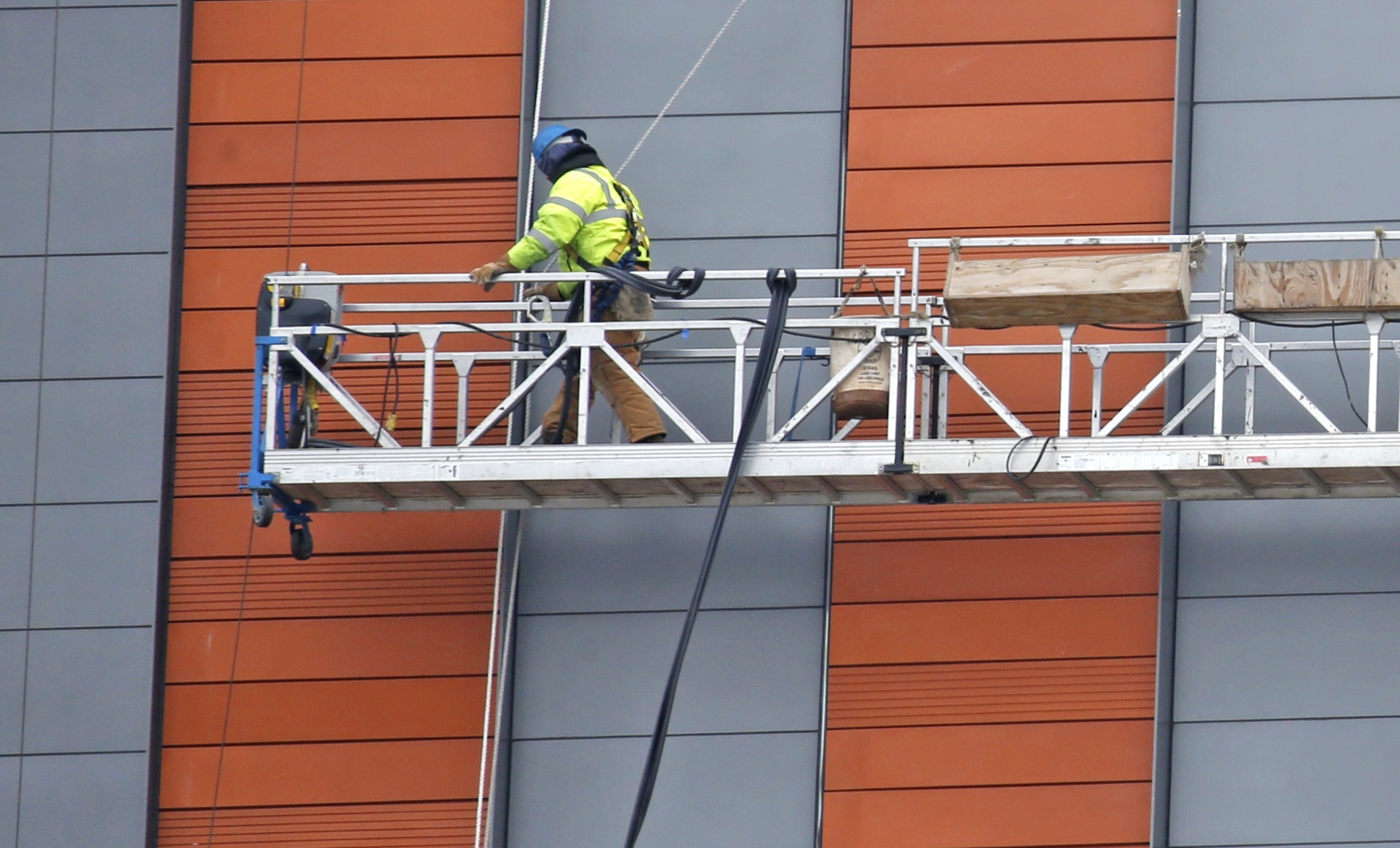 A worker installs the tiled outer siding of a new building on the Buffalo Niagara Medical Campus that will house UB's Jacobs School of Medicine and Biomedical Sciences. (Robert Kirkham/ Buffalo News)