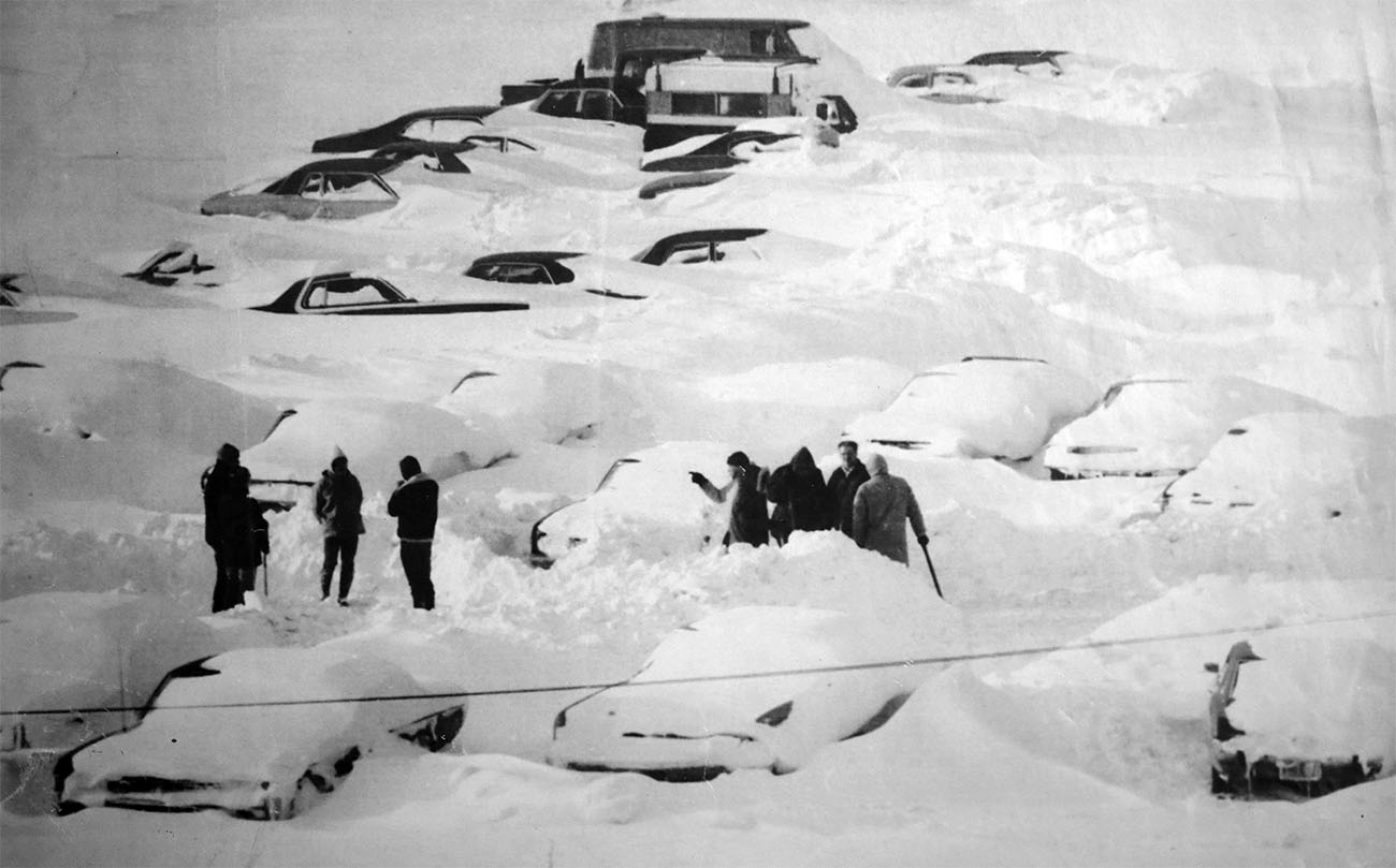 Blizzard of '77.  A group of people gather around their drifted over autos in a parking lot in the south part of Buffalo.  Feb. 2, 1977.  Though the mayor Banned all non-emergency driving in the city many people decided to try to at least dig out their autos or find where it was towed when crews were clearing major streets.  (The Buffalo History Museum)