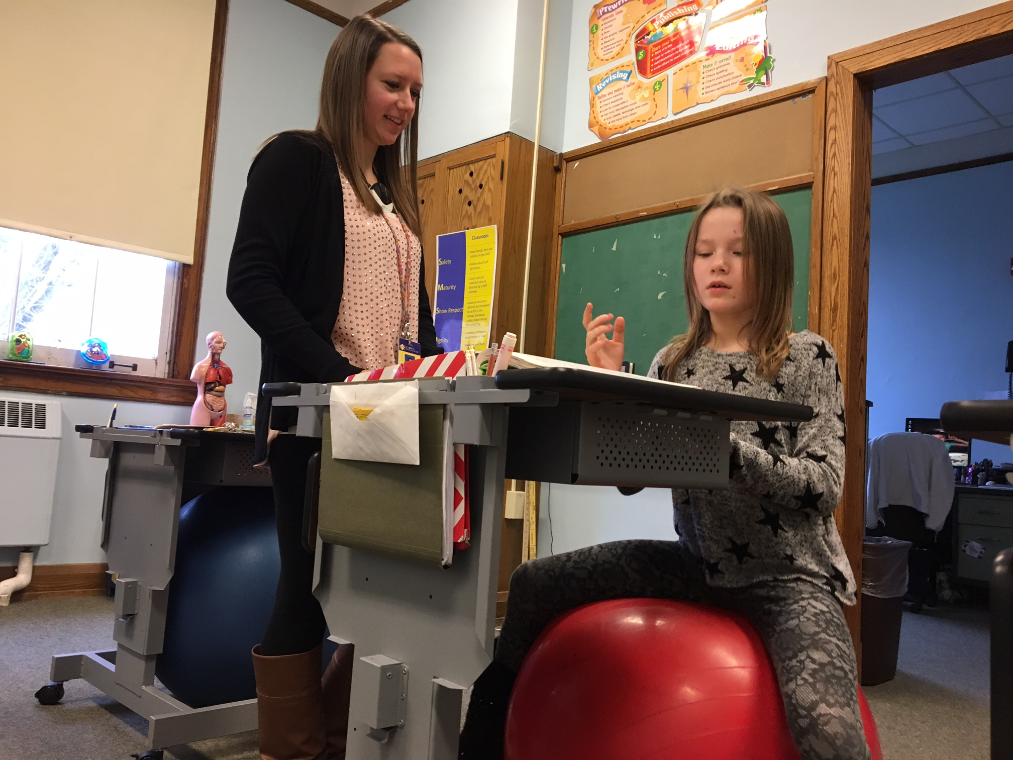St. Mary's School for the Deaf elementary teacher Sarah Niesyty and one of her students, Zarielle Ormsby, 8, a third-grader, like the Marvel Group adjustable stand up desks put into Niesyty's classroom at the start of the school year. (Photos by Scott Scanlon)