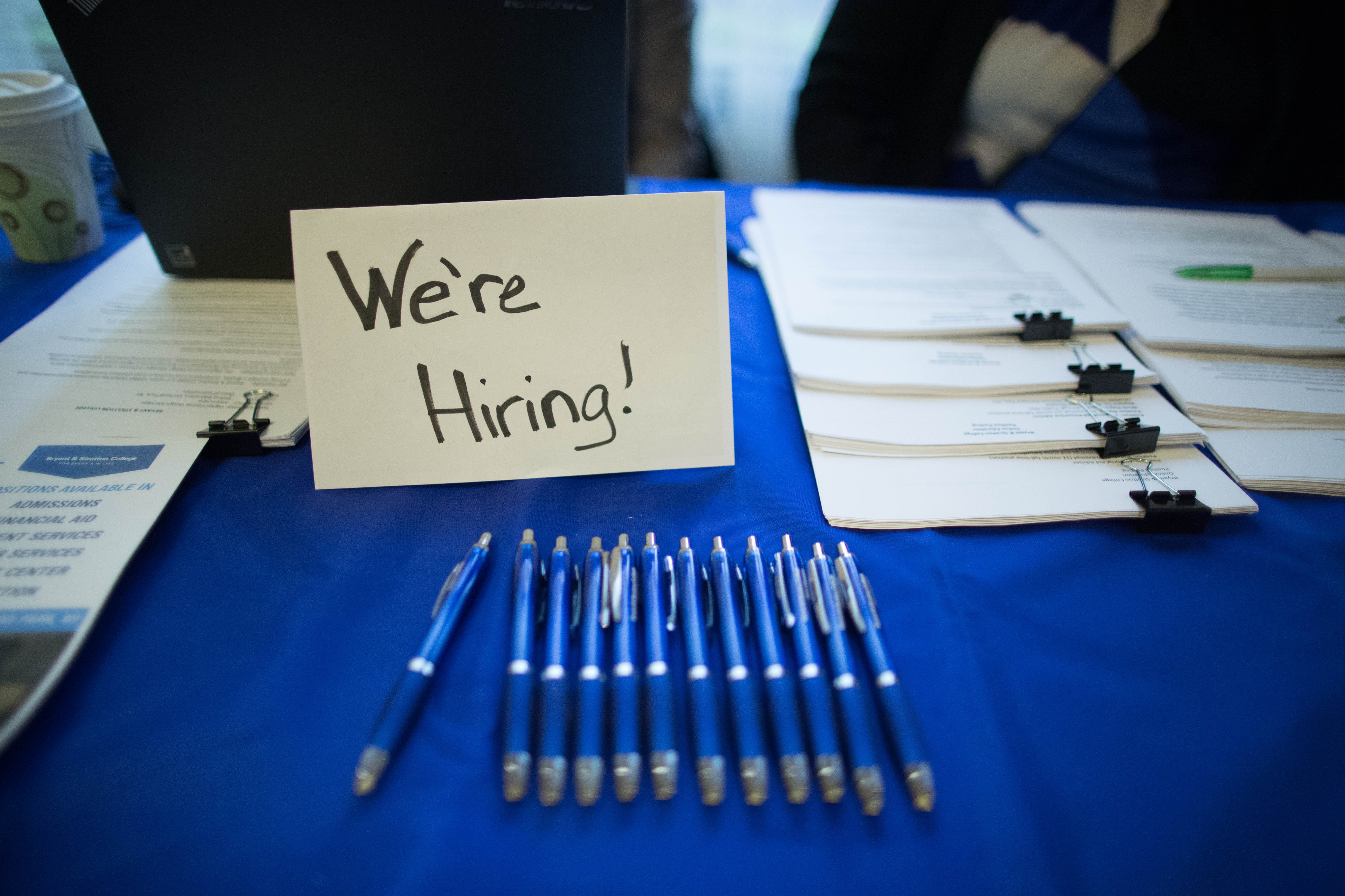A sign advertises employment on a vendor's table during the Jobsapalooza career fair at the Buffalo Niagara Marriott in Amherst in January.  (Derek Gee/Buffalo News)