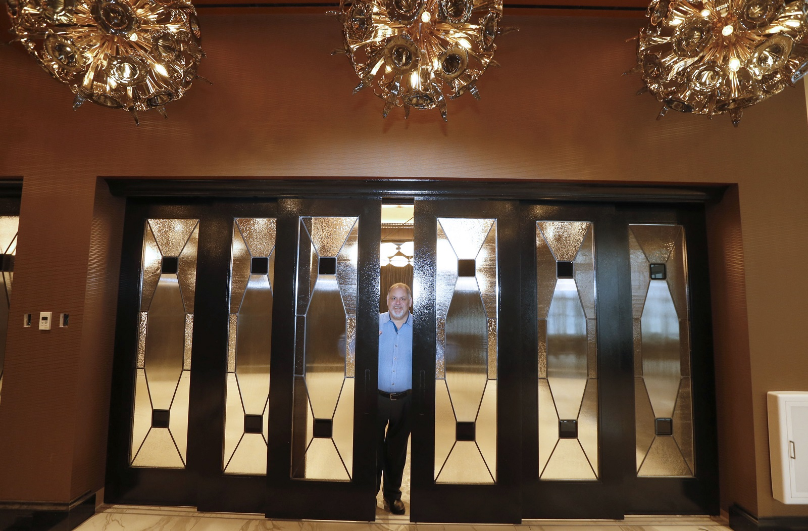 Owner Mark Croce tries out the new custom leaded glass door units in the restaurant area at the Curtiss Hotel. (Robert Kirkham/Buffalo News)