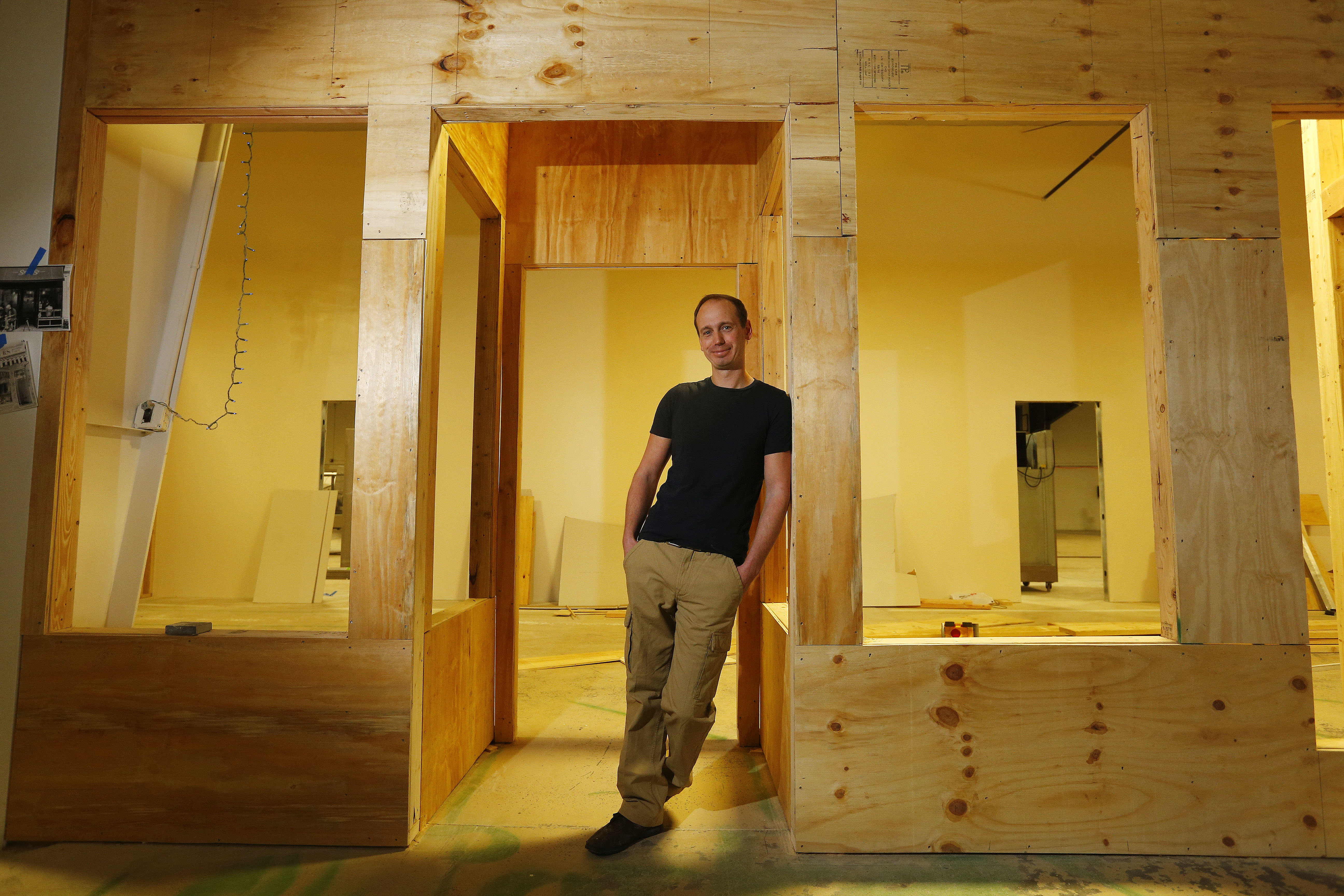 Damian Parker, owner of Parker's, stands with the framework of the British High Street he is recreating inside his warehouse in South Buffalo. (Mark Mulville/Buffalo News)