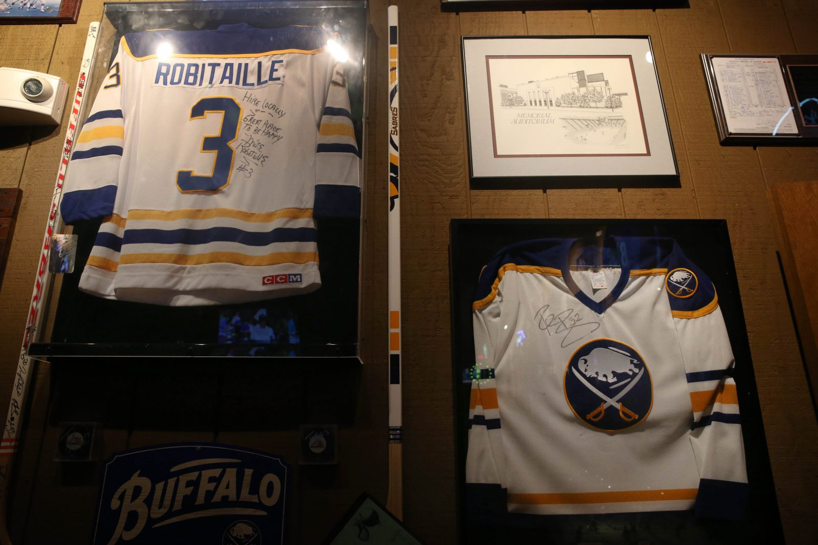 The walls at Buffalo Roadhouse Grill are filled with local sports memorabilia such as jerseys of retired Buffalo Sabres Mike Robitaille and Rob Ray. (Sharon Cantillon/Buffalo News)