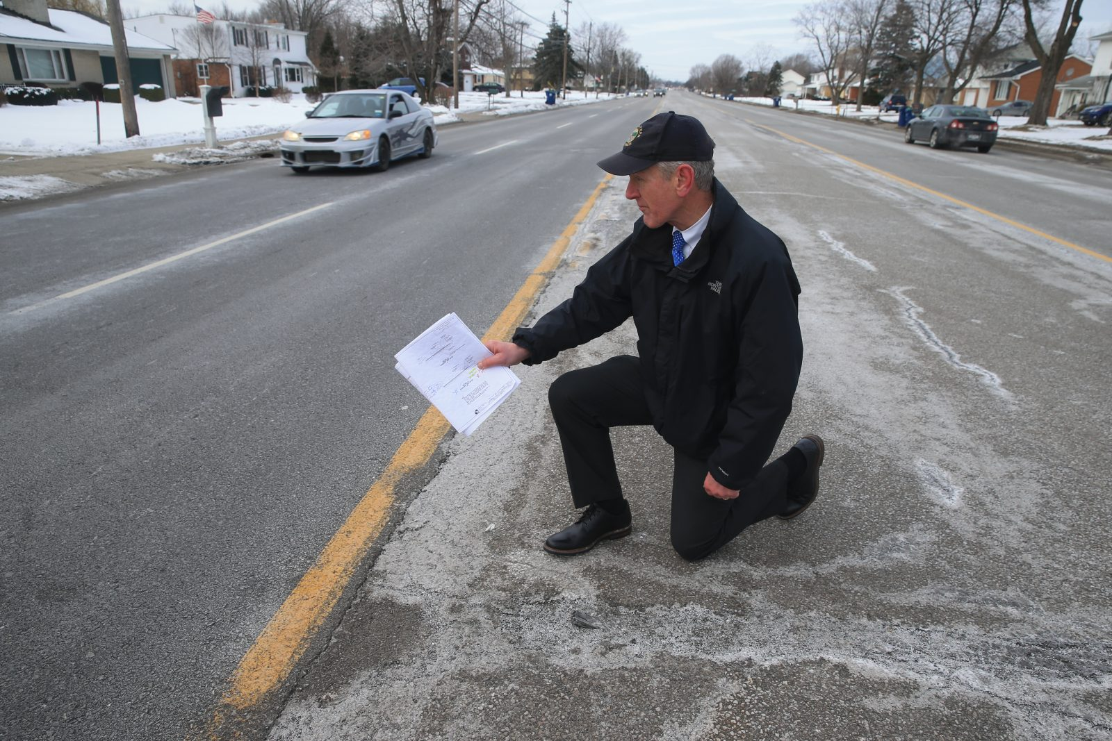 Charles A. Sickler, Erie County's director of engineering, checks out the pavement test strip option on Maple Road in Amherst that has become the county's preferred repaving option after a year-long experiment. (John Hickey/Buffalo News)