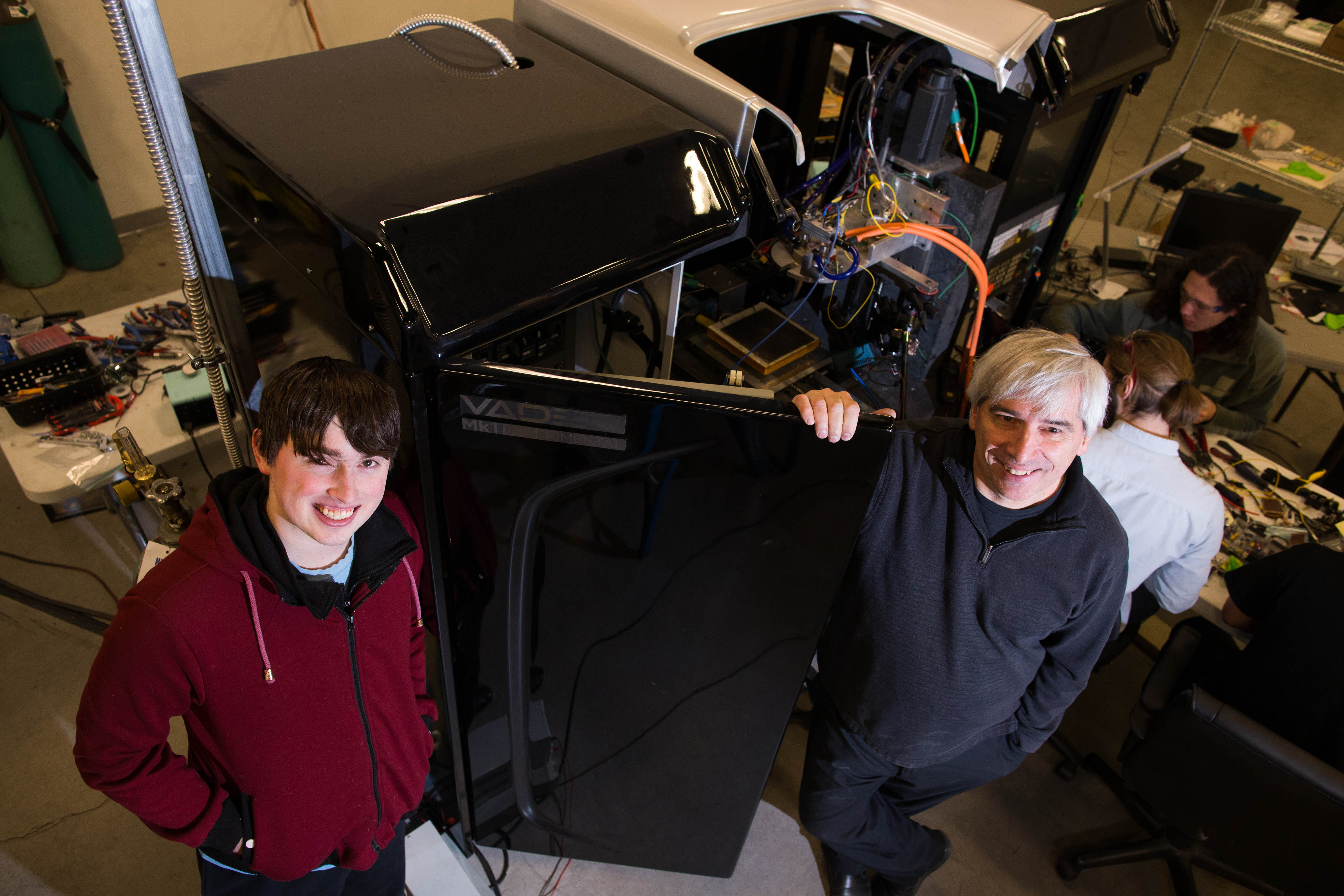 Zack and Scott Vader founded Vader Systems in the basement of their home five years ago. Here they pose with the Vader Mk1 Experimental liquid metal printer they designed and are manufacturing at the Vader Systems facility in Amherst.  (Derek Gee/Buffalo News)
