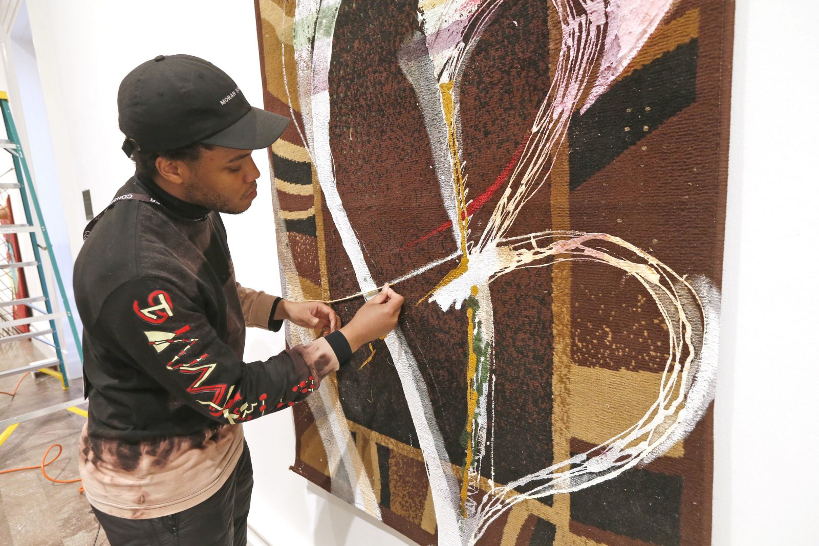 Artist Eric N. Mack of New York City tweaks one of his works called 'For Us by Us' at the Albright-Knox Art Gallery.  (Robert Kirkham/Buffalo News)