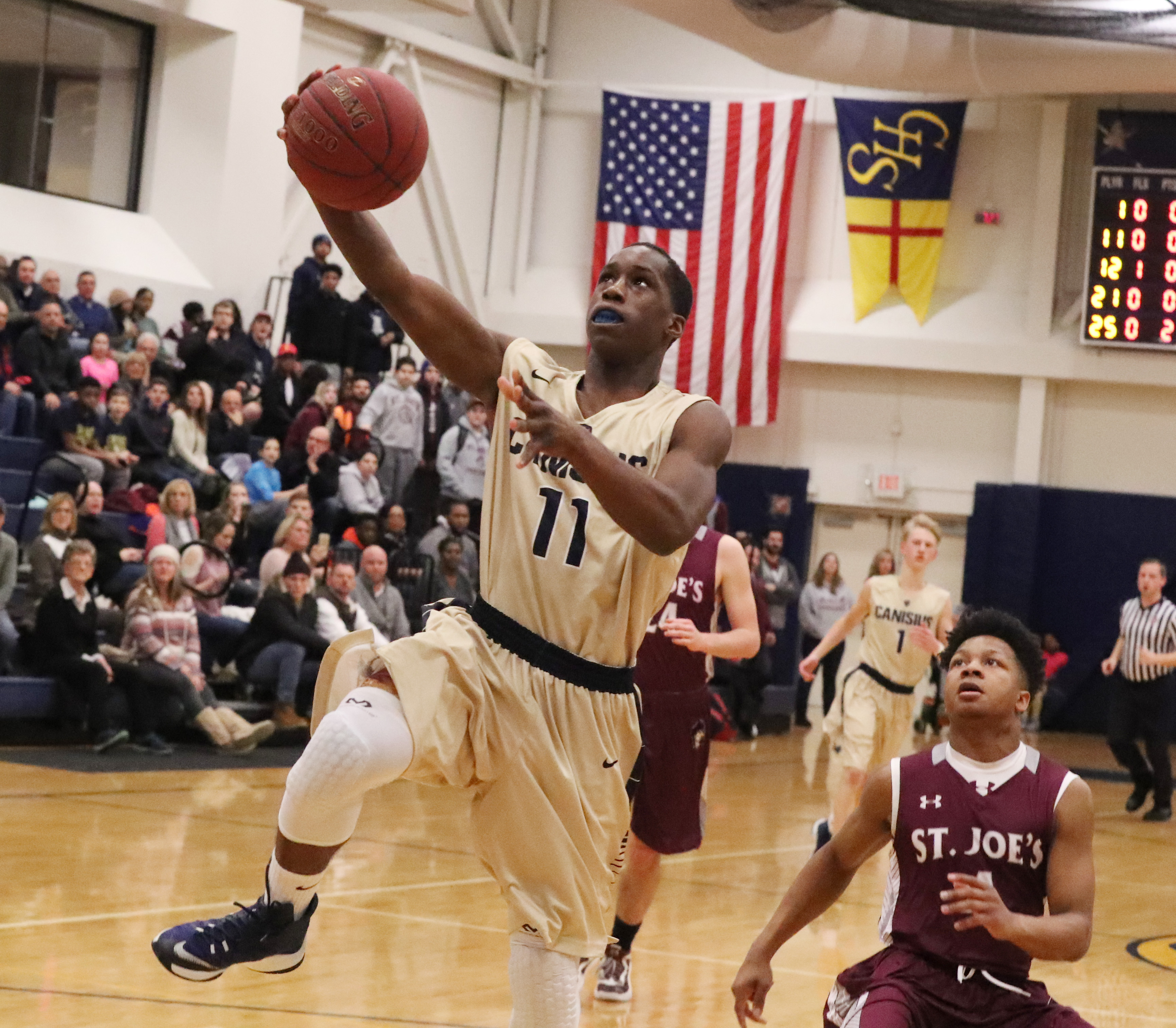 Canisius' Joe Jamison score an easy basket over St. Joe's Naseer Jackson in the second quarter of Friday's game. (James P. McCoy/Buffalo News)