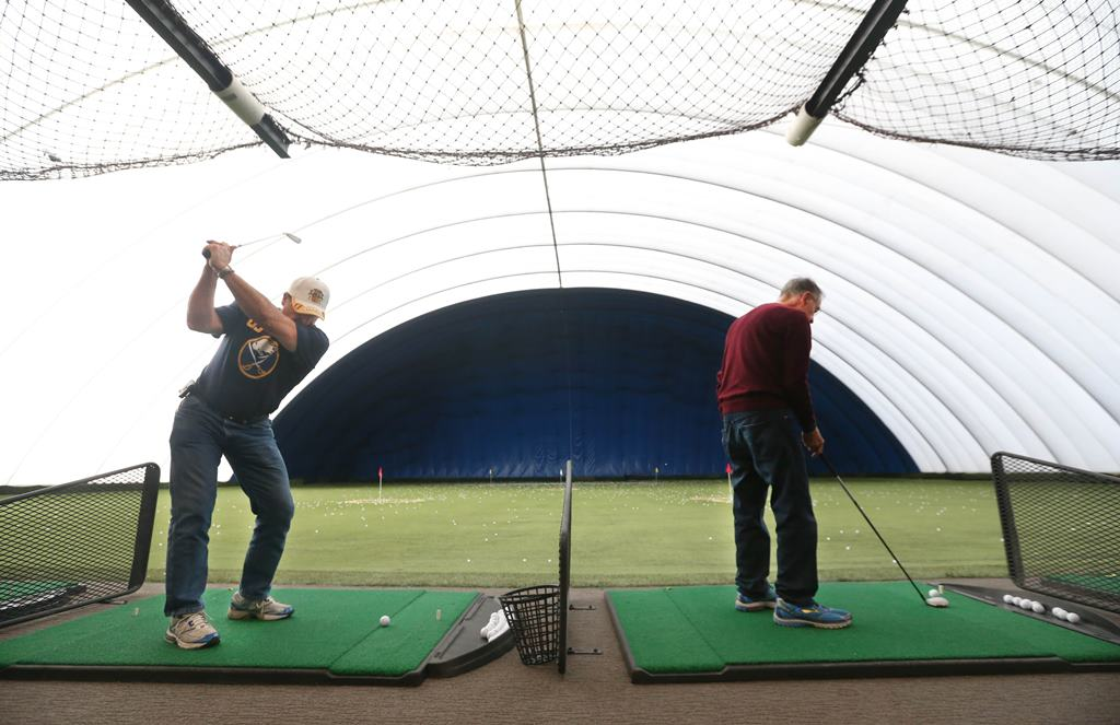 Rick Marzullo, left, of West Seneca and Nick Schmitt, of Buffalo, hit a bucket of balls, in the new hitting stalls at the Dome in Clarence, which reopened Feb. 10. (Sharon Cantillon/Buffalo News)