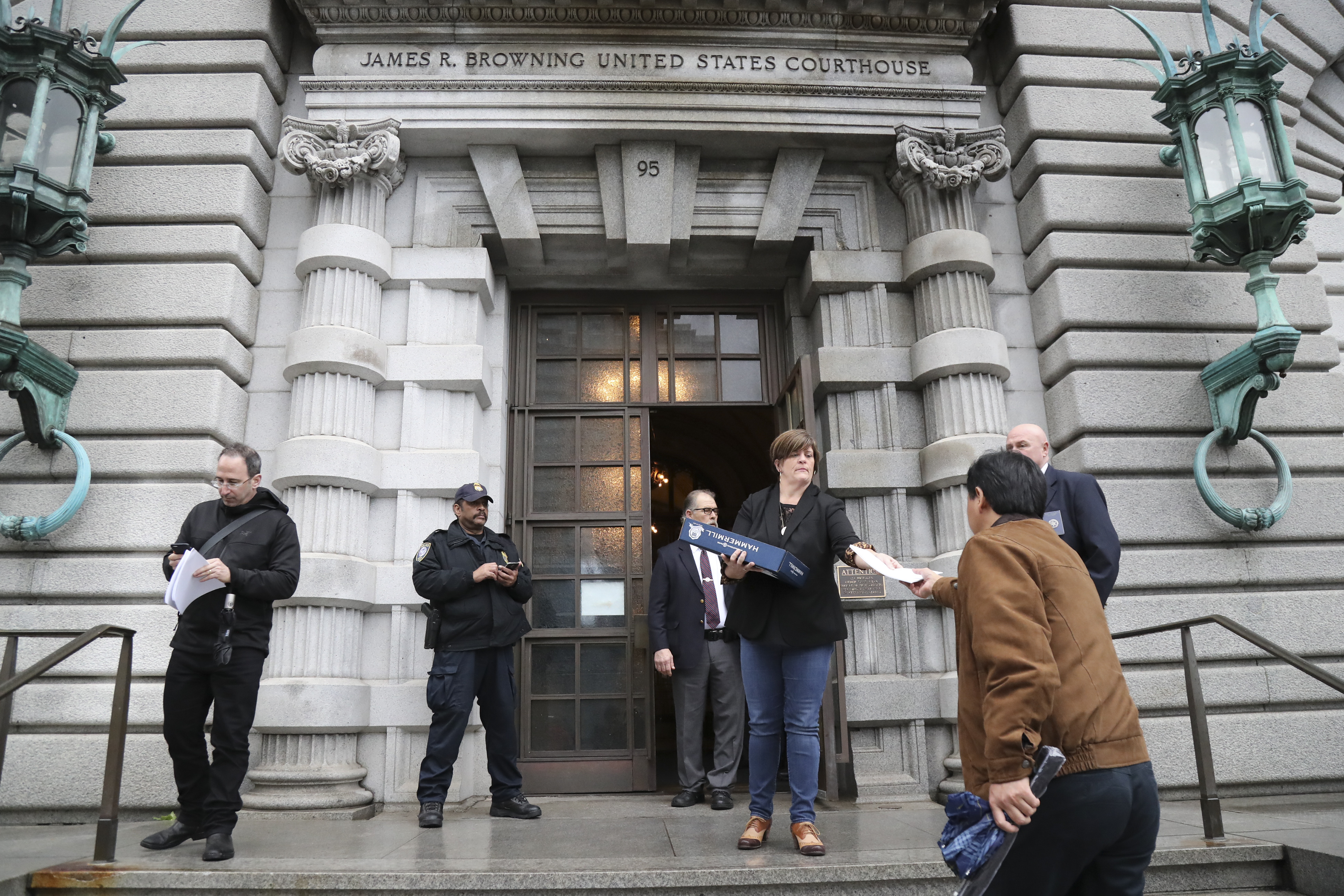 A woman hands out the 9th Circuit Court of Appeals' ruling against President Trump's travel ban, outside the courthouse in San Francisco, Feb. 9, 2017. The court's ruling against the travel ban could be quickly appealed to the short-handed U.S. Supreme Court. (Jim Wilson/The New York Times)