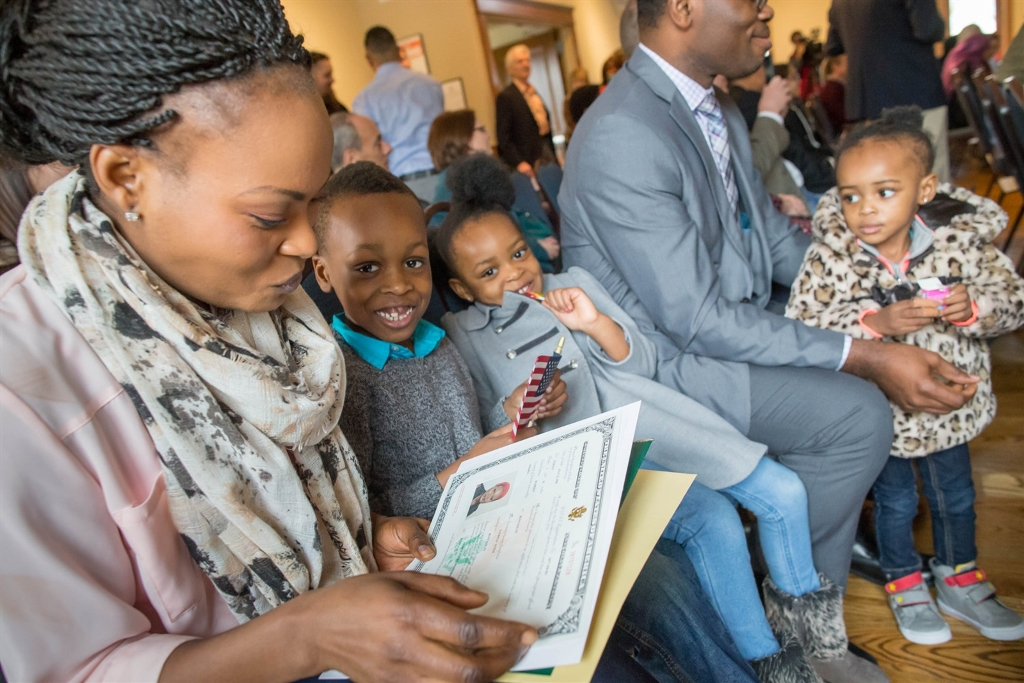New U.S. citizen Patricia Suteh of Nigeria, looks over her new certificate of naturalization with her children, son Kemene, 5, daughters, Kezor, 3, and Lenu, 2, and husband, K.C. (Derek Gee/Buffalo News)