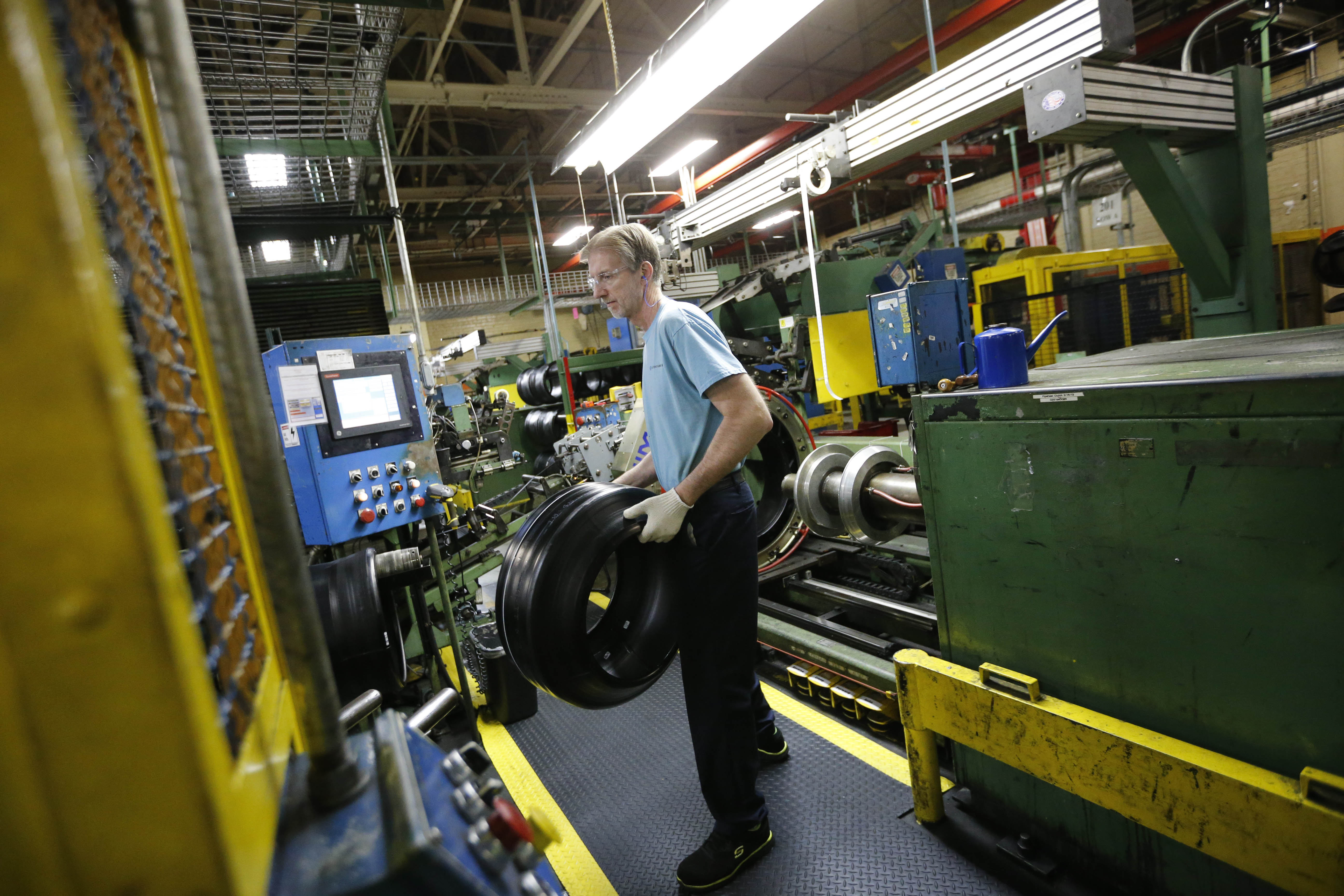 A second-stage tire builder removes a tire from a machine in the Sumitomo Rubber USA tire manufacturing plant in Tonawanda.  (Derek Gee/Buffalo News file photo)