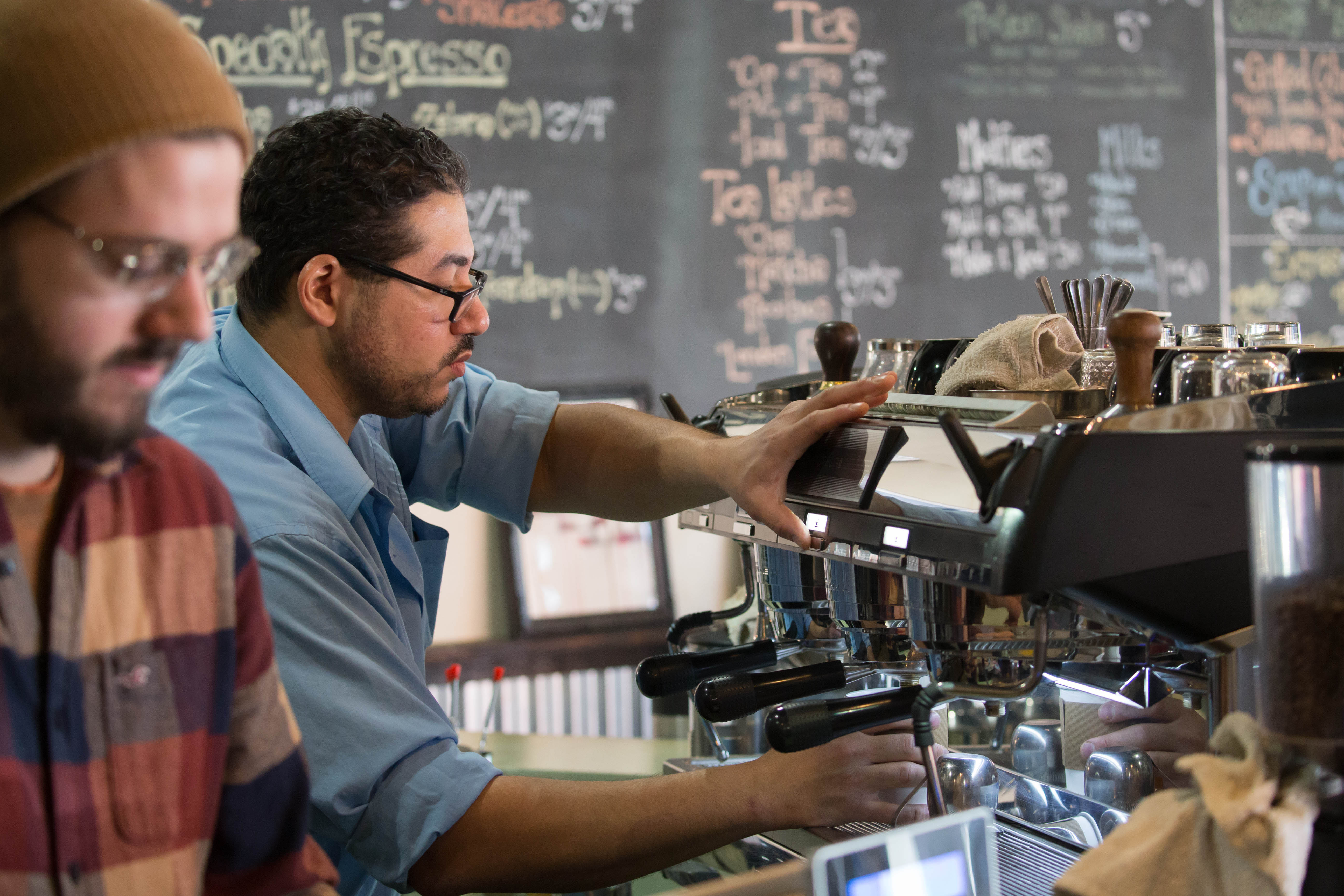 Hamada Saleh, owner of Caffeology on Allen Street, hopes to capitalize on the growing Buffalo Niagara Medical Campus.  He makes an espresso for a customer during the morning rush as chef Nate Bailey tends to the register.  (Derek Gee/Buffalo News)