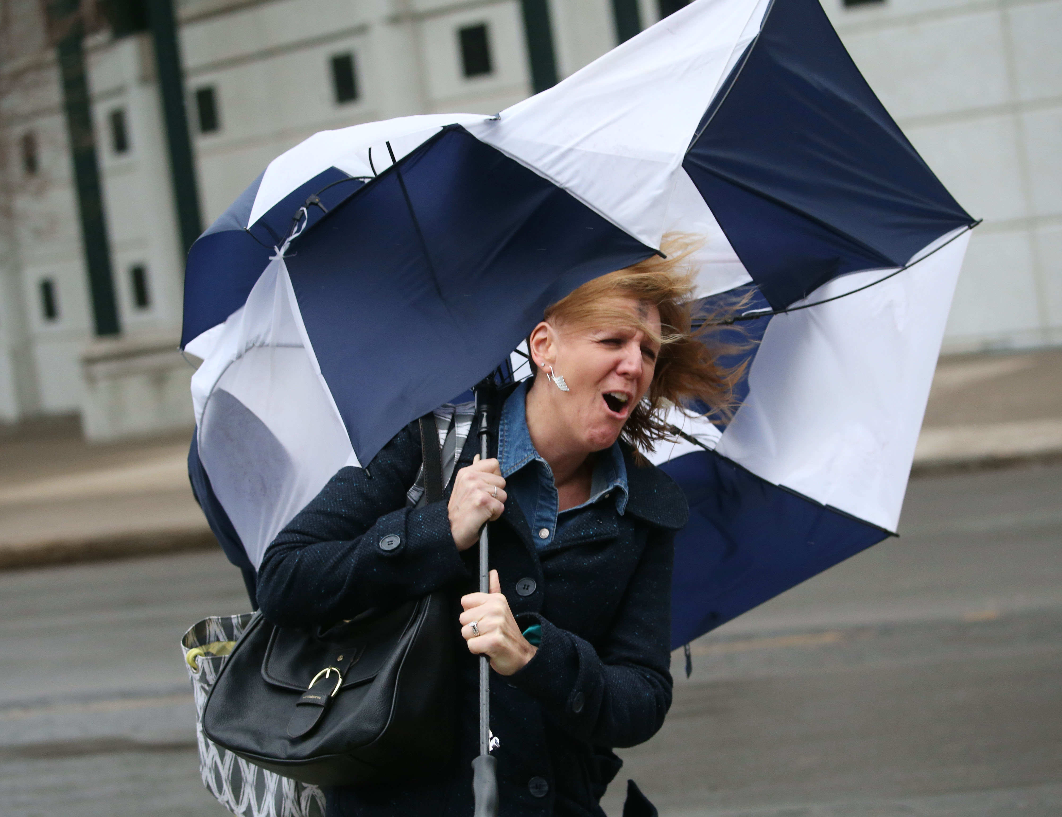 Karen Walkowiak's umbrella meets an early demise as she walks to her car after work on Washington St. during high winds in the late afternoon,  Wednesday, March 1, 2017.  (Sharon Cantillon/Buffalo News)