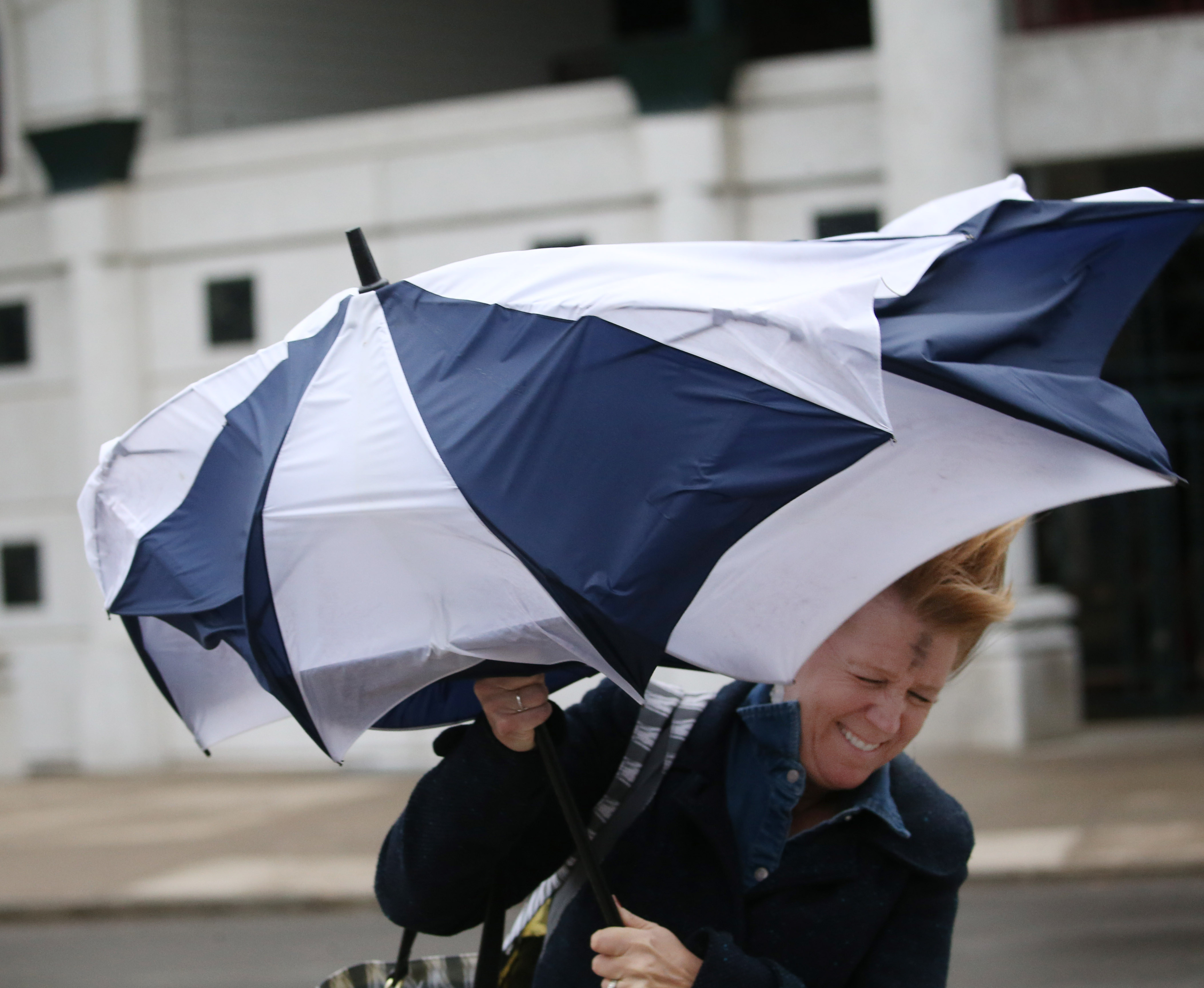 Karen Walkowiak's umbrella meets an early demise as she walks to her car after work on Washington Street in the late afternoon of March 1, 2017. (Sharon Cantillon/Buffalo News)