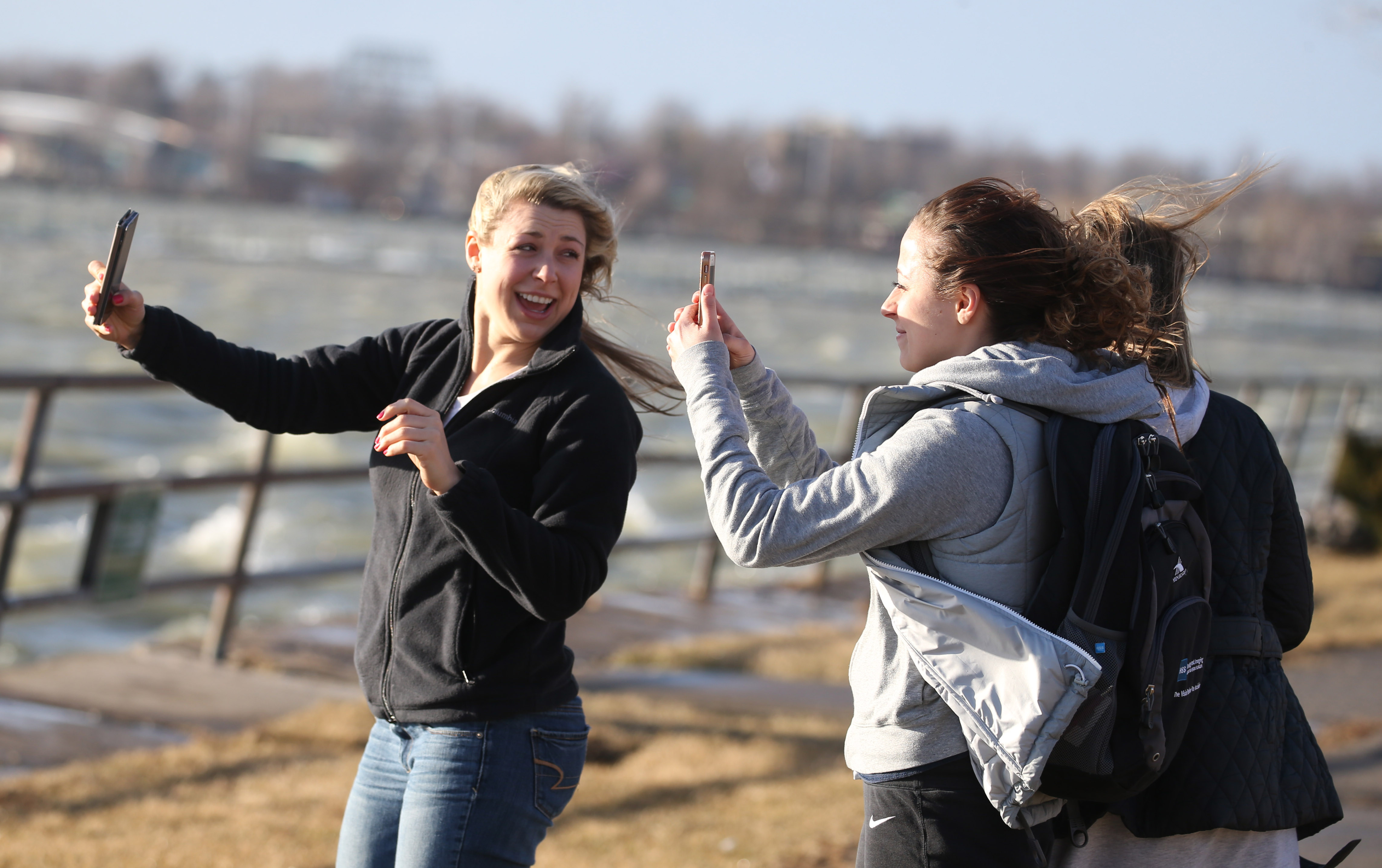 If it's warm weather you want, you should be hoping for downslope winds to blow in. Here, D'Youville students Catherine Cotrupe, Esada Kucevie and Amy Liszewski take pictures as a strong wind blows in off the lake at LaSalle Park on March 8.  (Sharon Cantillon/News file photo)