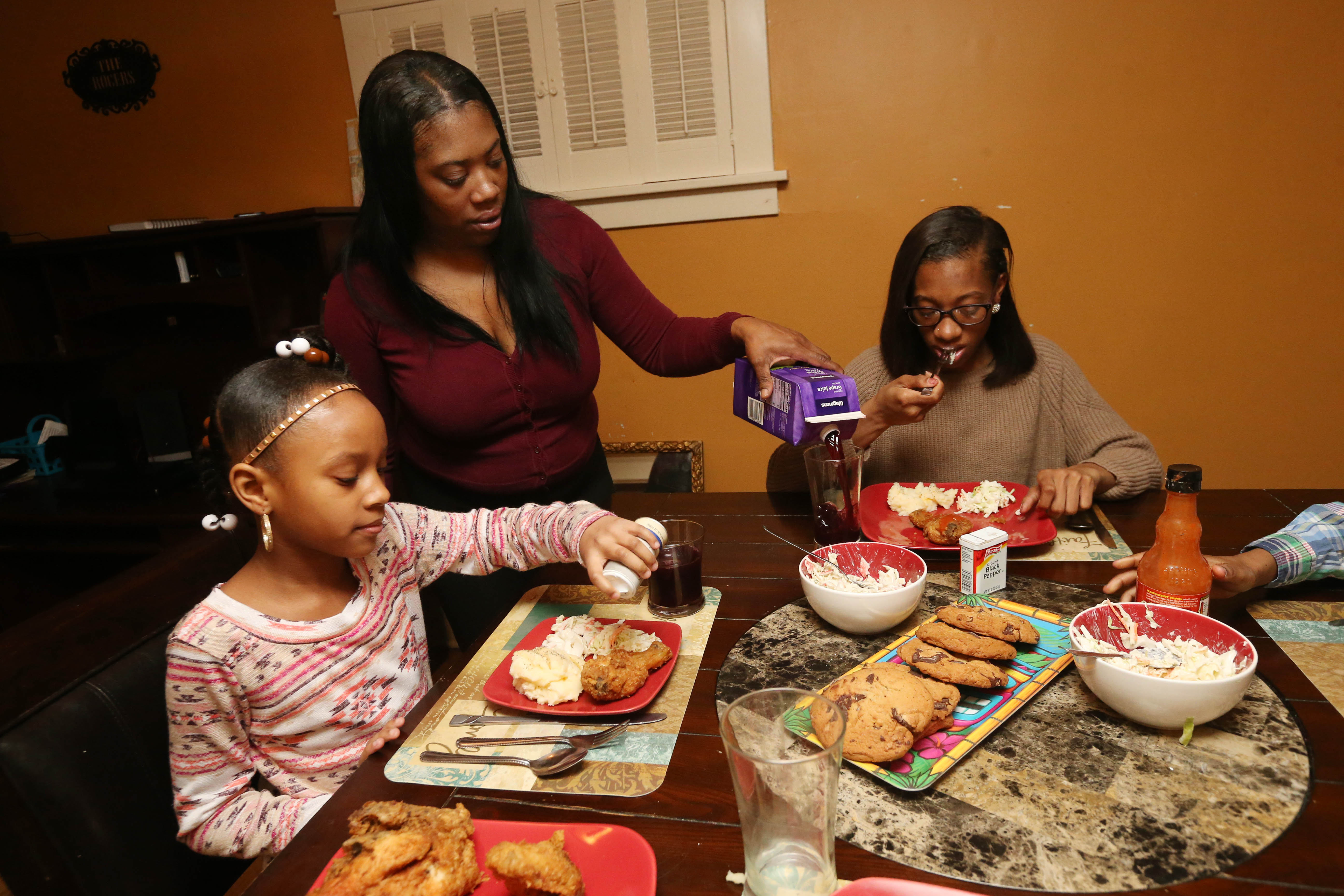 Aneesha Richardson-Rogers having dinner with her family. The mother of three doesn't receive public assistance from Social Services except for the HEAP benefits, which has helped her keep up with her rent and other bills. Pictured here with  stepdaughter Dynasti Rogers, 8, left, daughter Anaya Smith, 15, and son Amir Chambers, 9.  (Sharon Cantillon/Buffalo News)