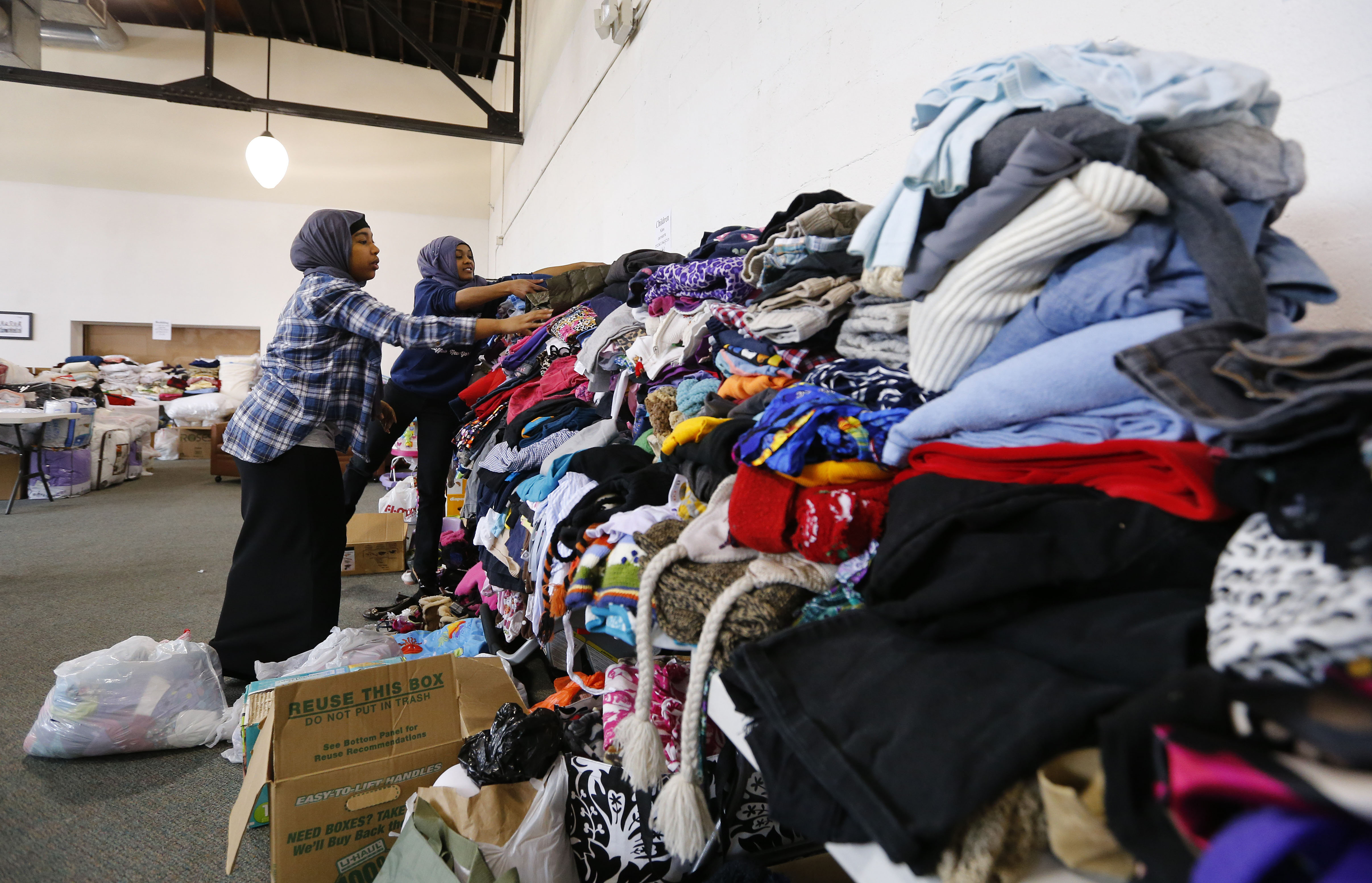 Event organizers Laila Ismail, left, and Juweria Dahir, right, sort through some of the donated clothes for the roughly 90 victims of last weekend's Lafayette Apartment fire at the Jericho Road Community Health Center in Buffalo Saturday, March 18, 2017.  (Mark Mulville/Buffalo News)